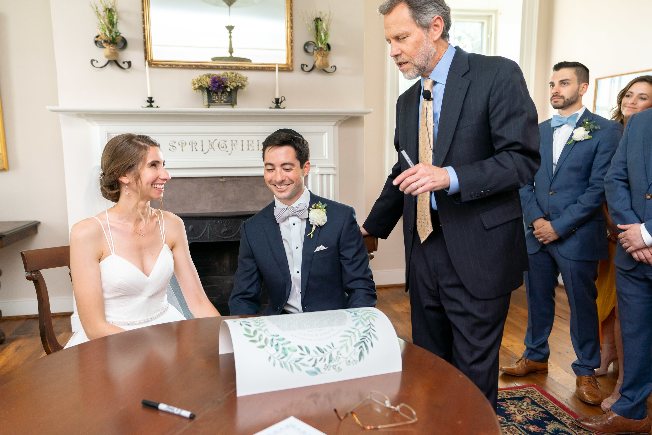 Bride and groom signing the ketubah in a side room at Springfield Manor