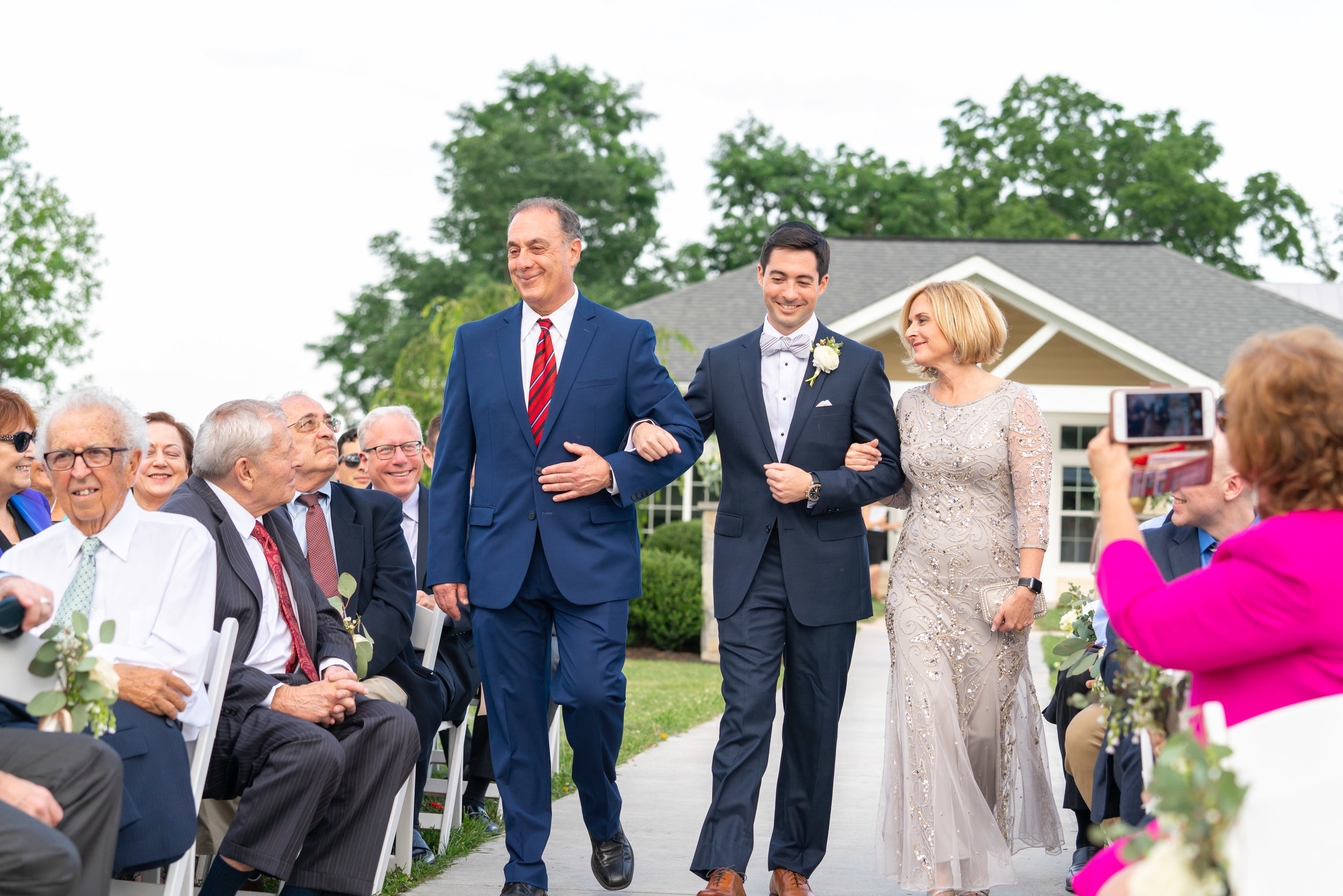 Groom's parents walking down the aisle during ceremony at Springfield Manor Winery