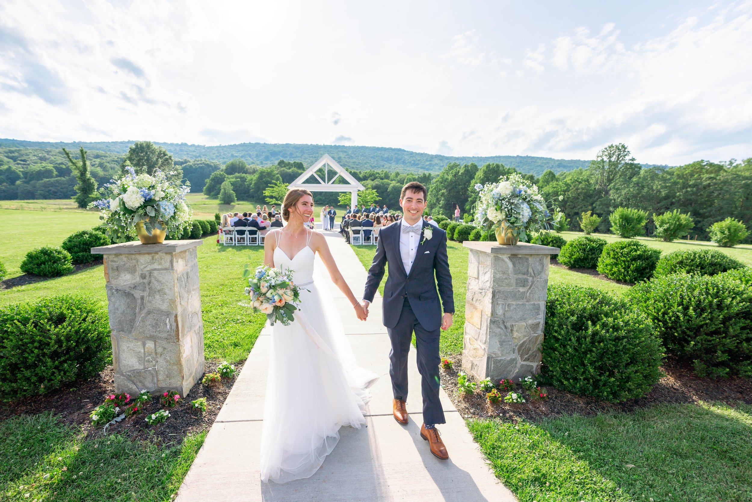 Bride and groom in front of ceremony site and sugarloaf at Springfield Manor winery and distillery