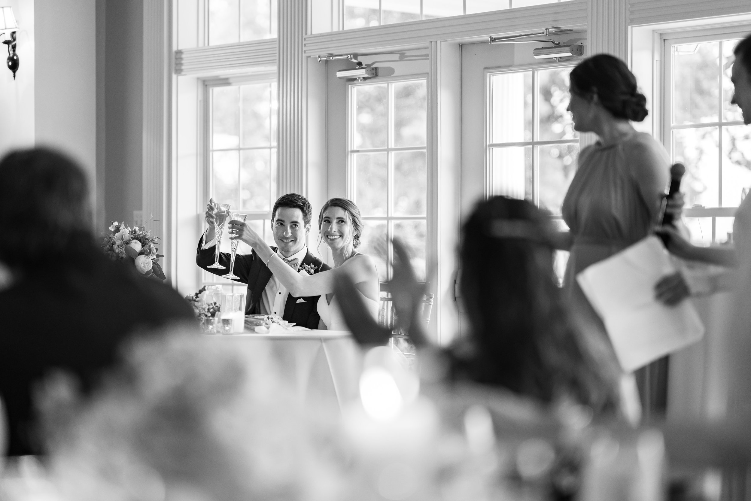 Black and white photo of bride and groom cheersing during bridesmaid speech