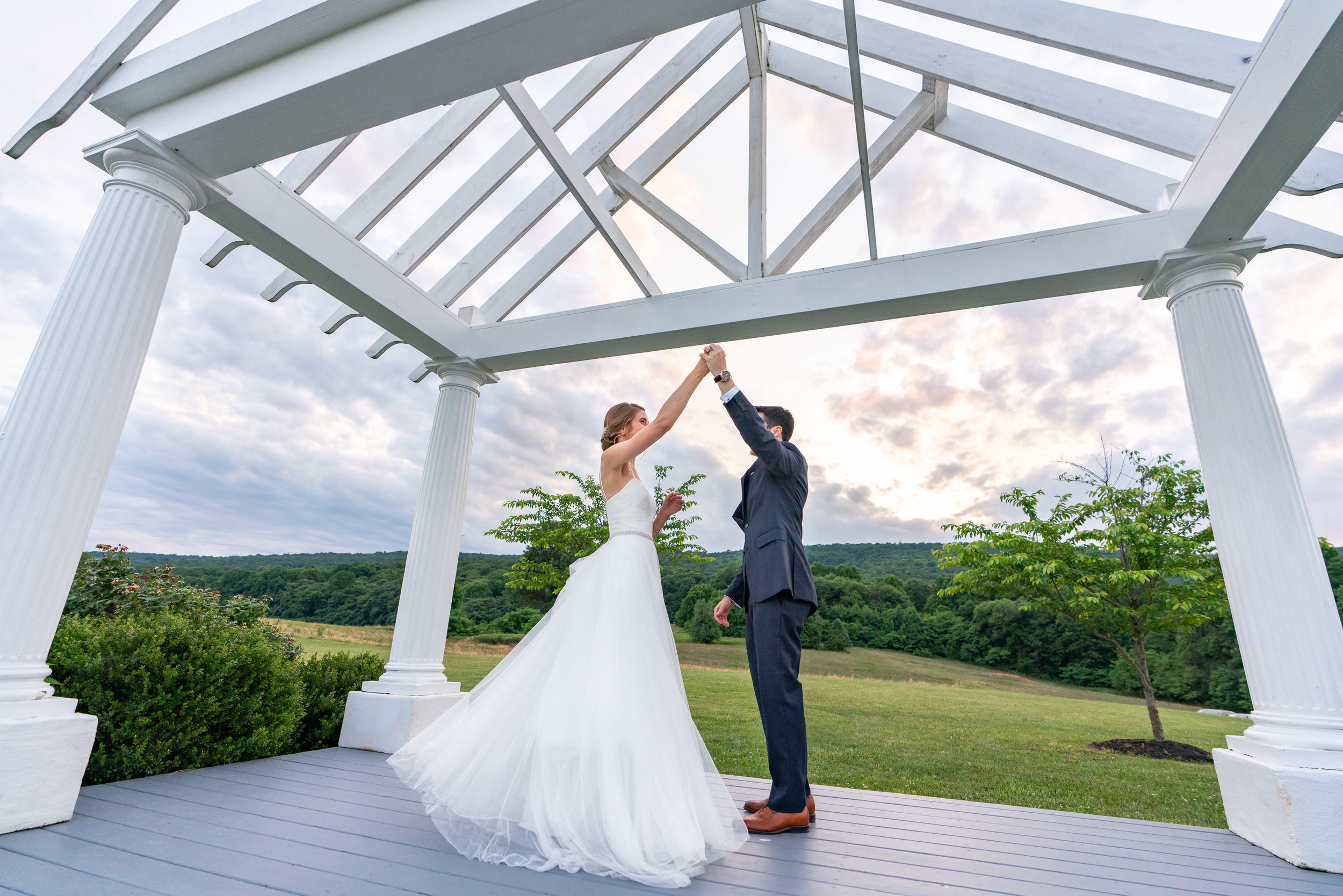 Groom twirling bride under incredible awning and sunset over sugarloaf mountain wedding venue