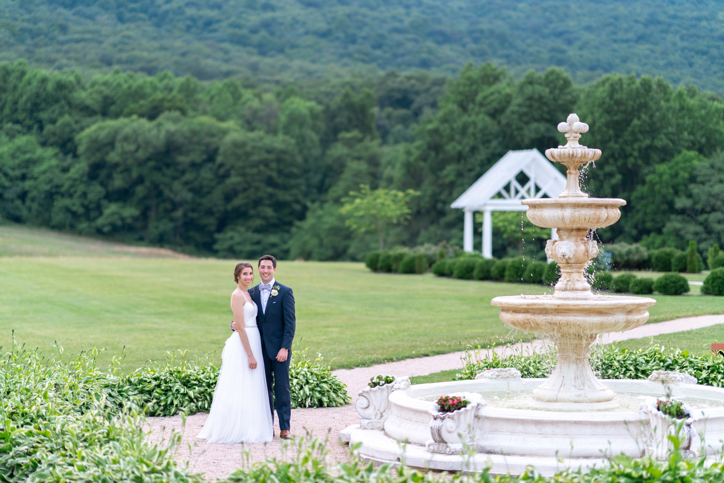 Bride and groom standing near fountain under sugarloaf mountain wedding venue