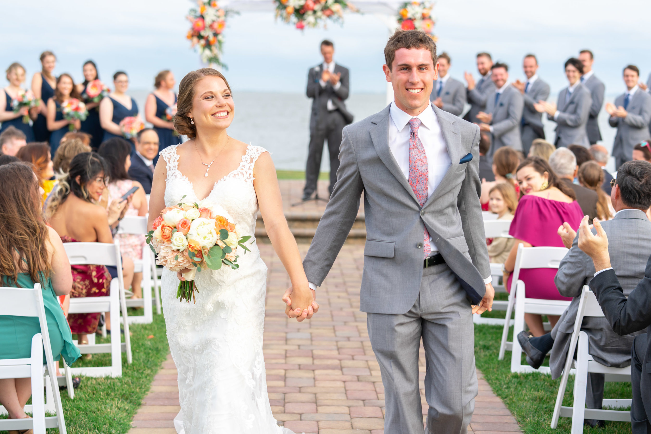 Bride and groom smiling holding hands walking down the aisle at Rehoboth Beach Country Club