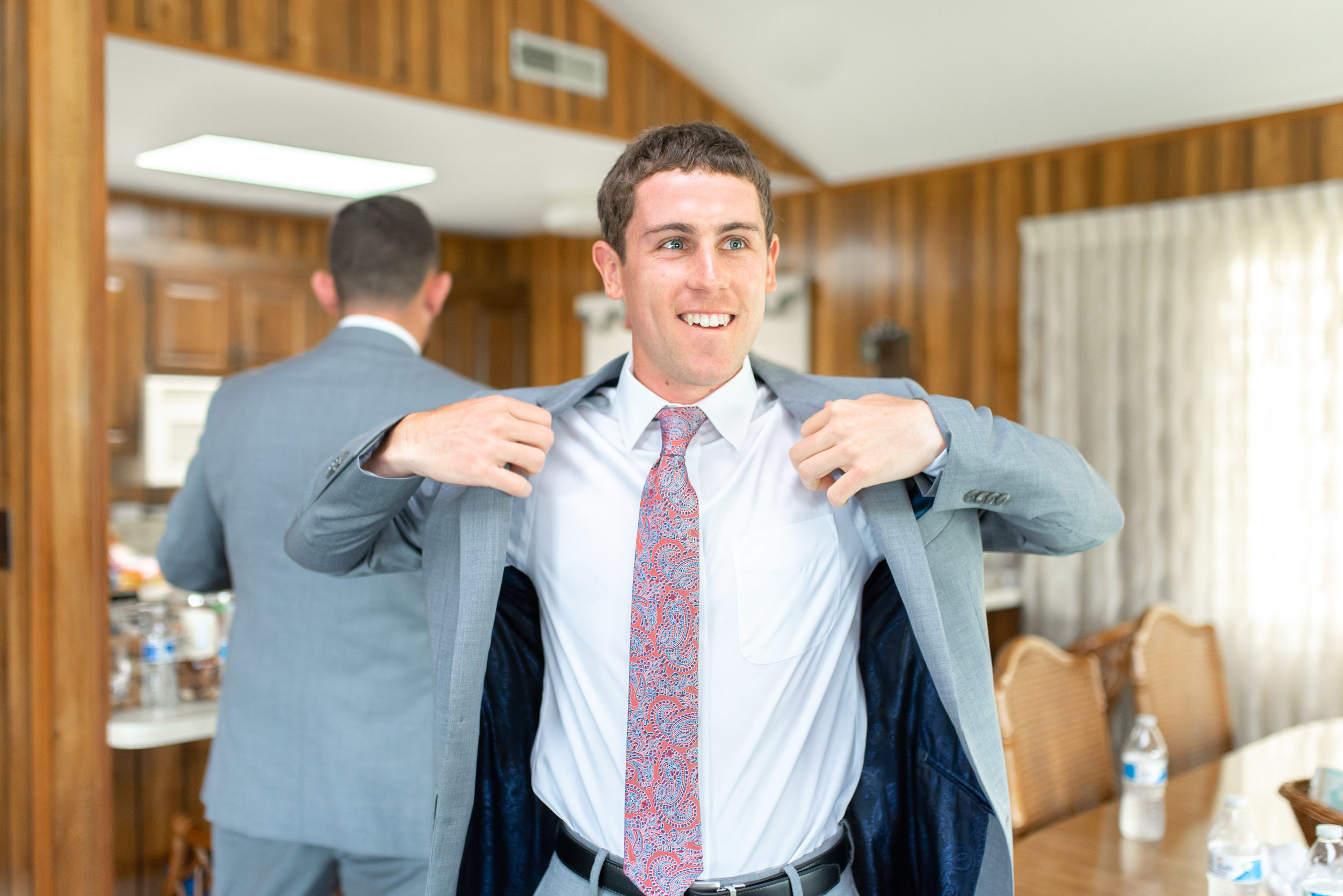 Groom putting on light gray jacket with purple tie for beach wedding