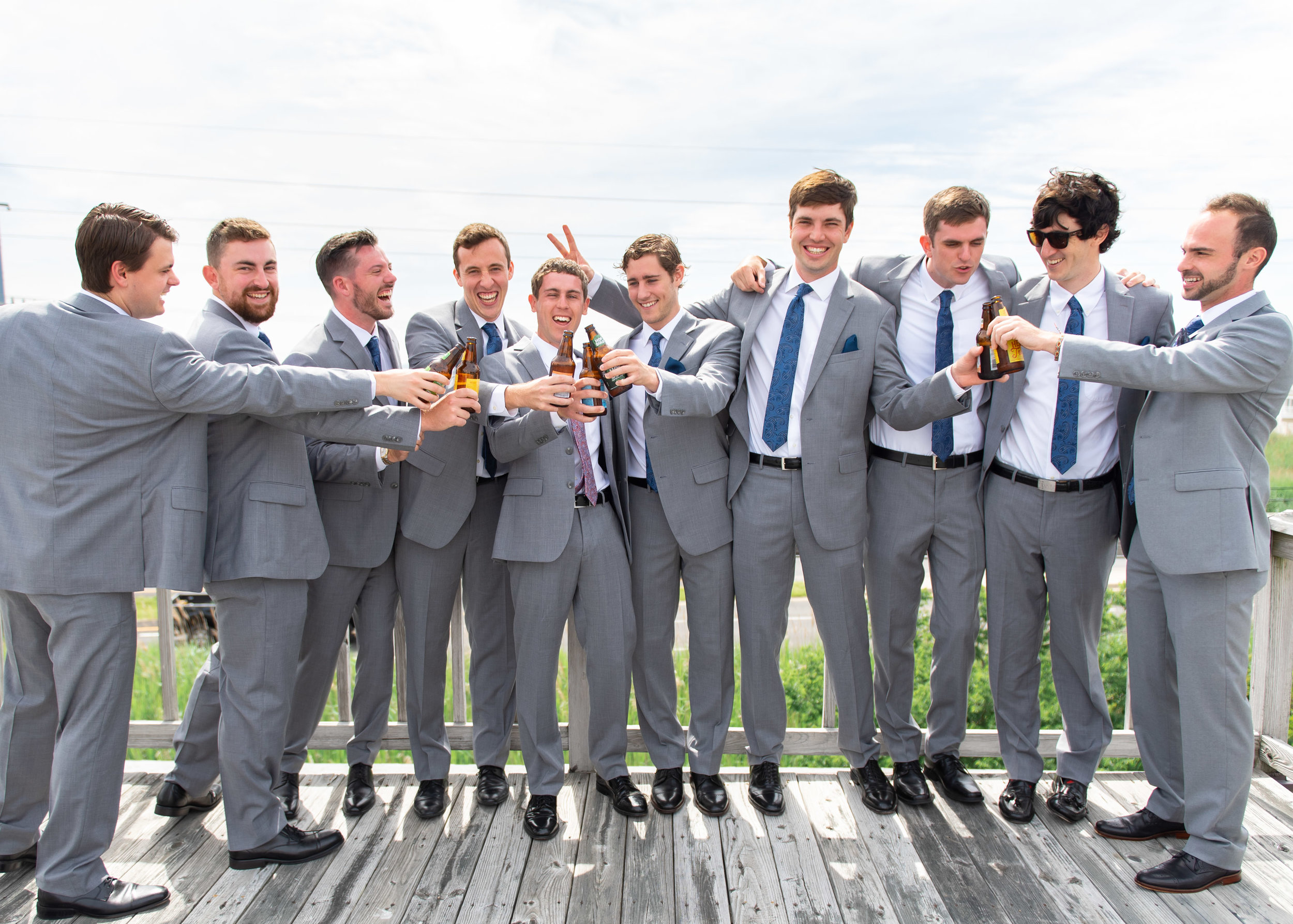 Groom and groomsmen toasting on the deck before wedding ceremony