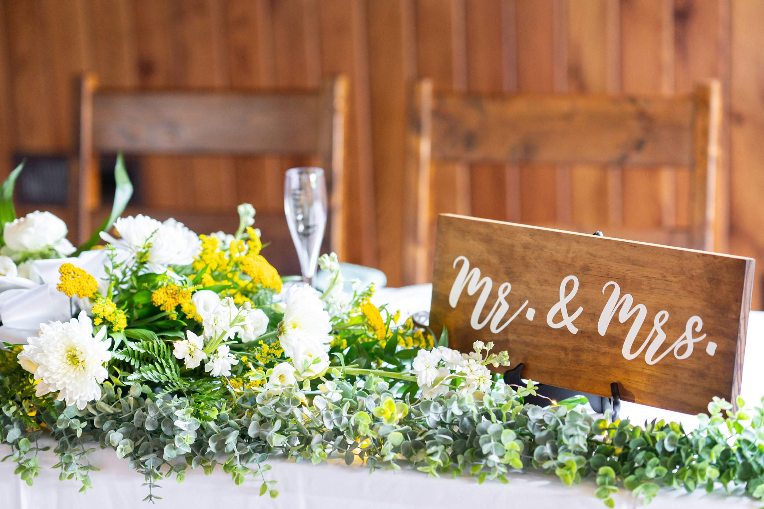 Beautiful Mr and Mrs sign with greenery on sweetheart table