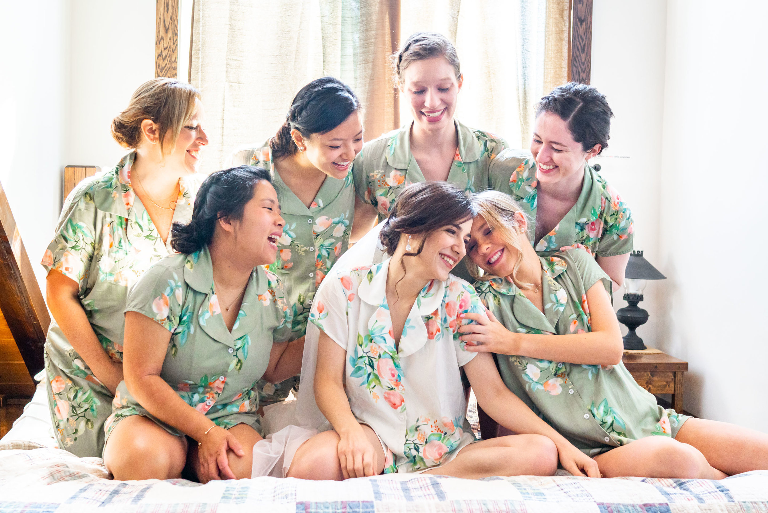 Bride and bridesmaids laughing on the bed at Shenandoahs elopement wedding