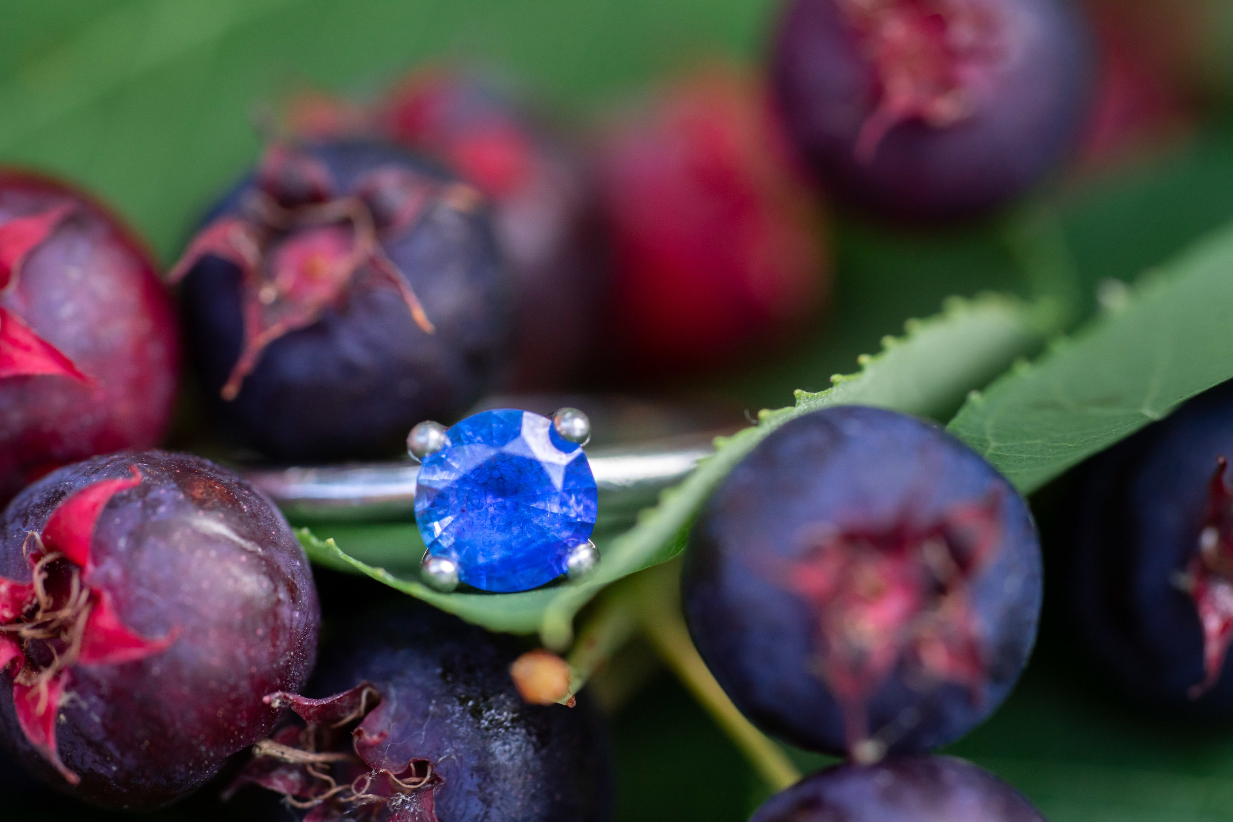 blue sapphire or blue emerald engagement ring on berries