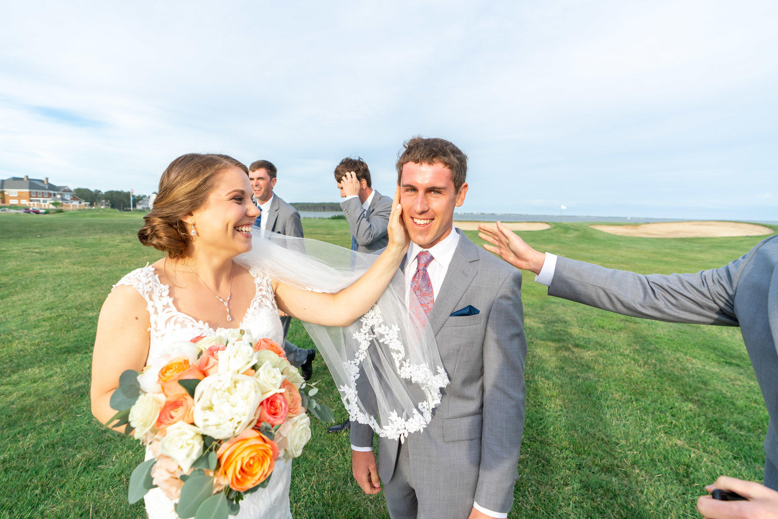 bride with her hand on grooms cheek and ocean in the background