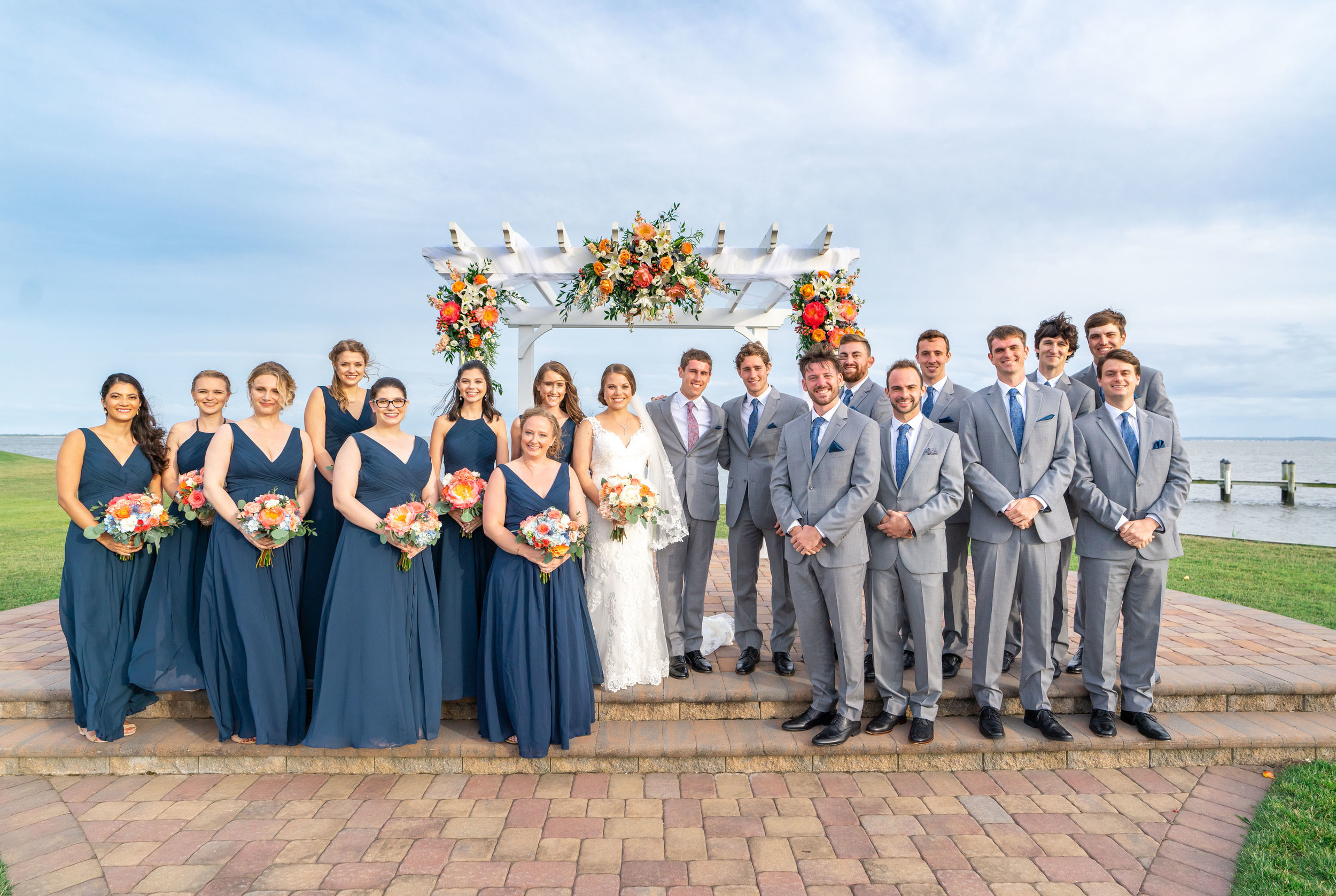 bride groom and bridal party under arbor at rehoboth beach country club