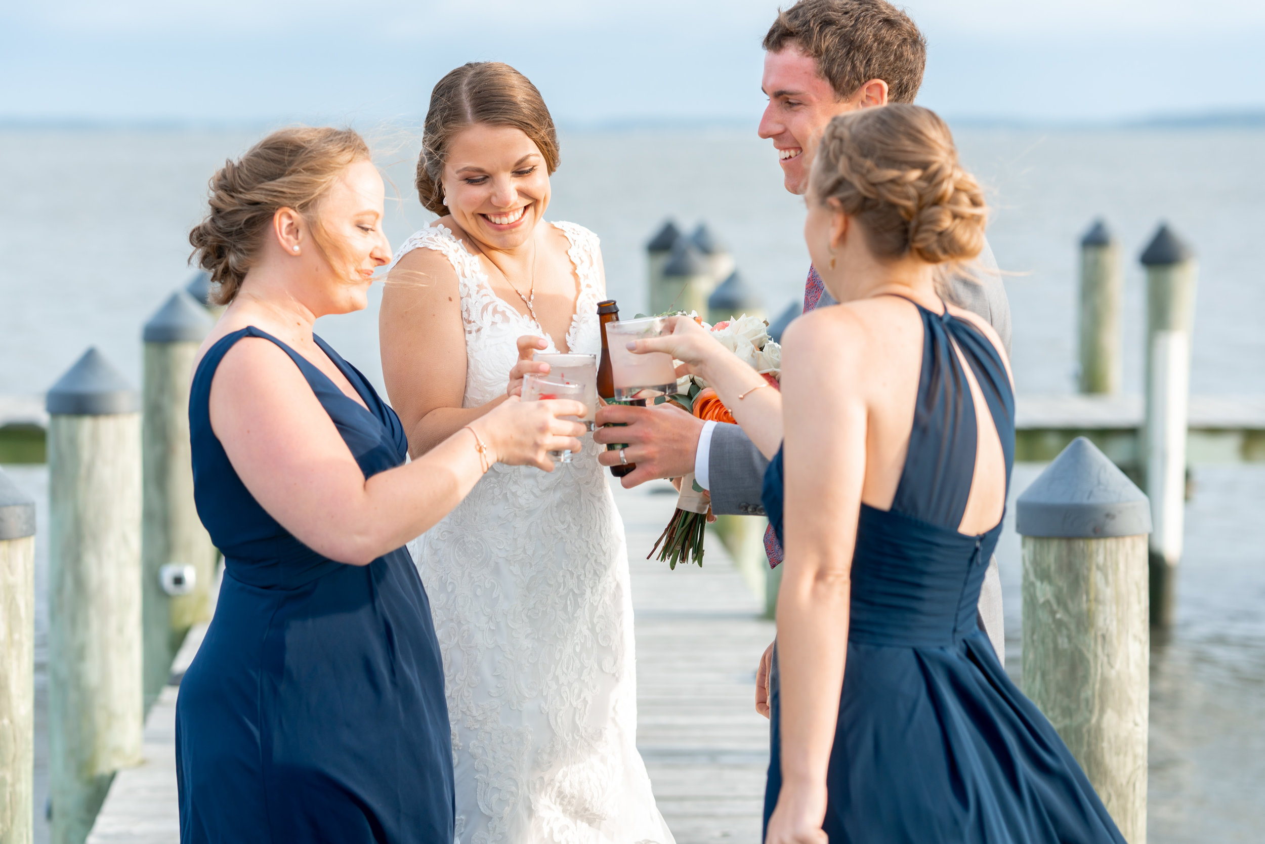 Bridesmaids bring out drinks to the bride and groom on the dock pier