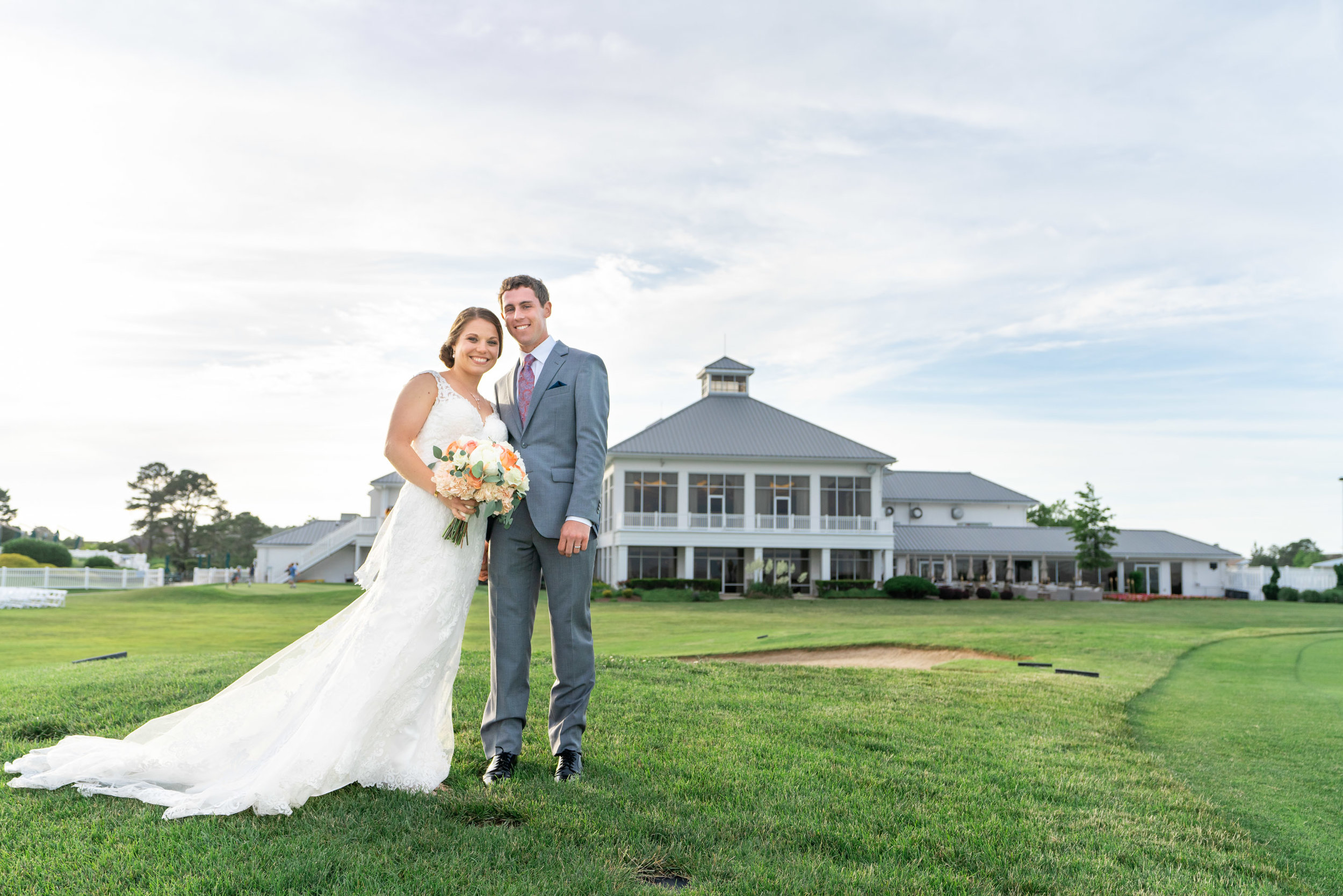 Bride and groom standing in front of Rehoboth Beach Country Club during sunset