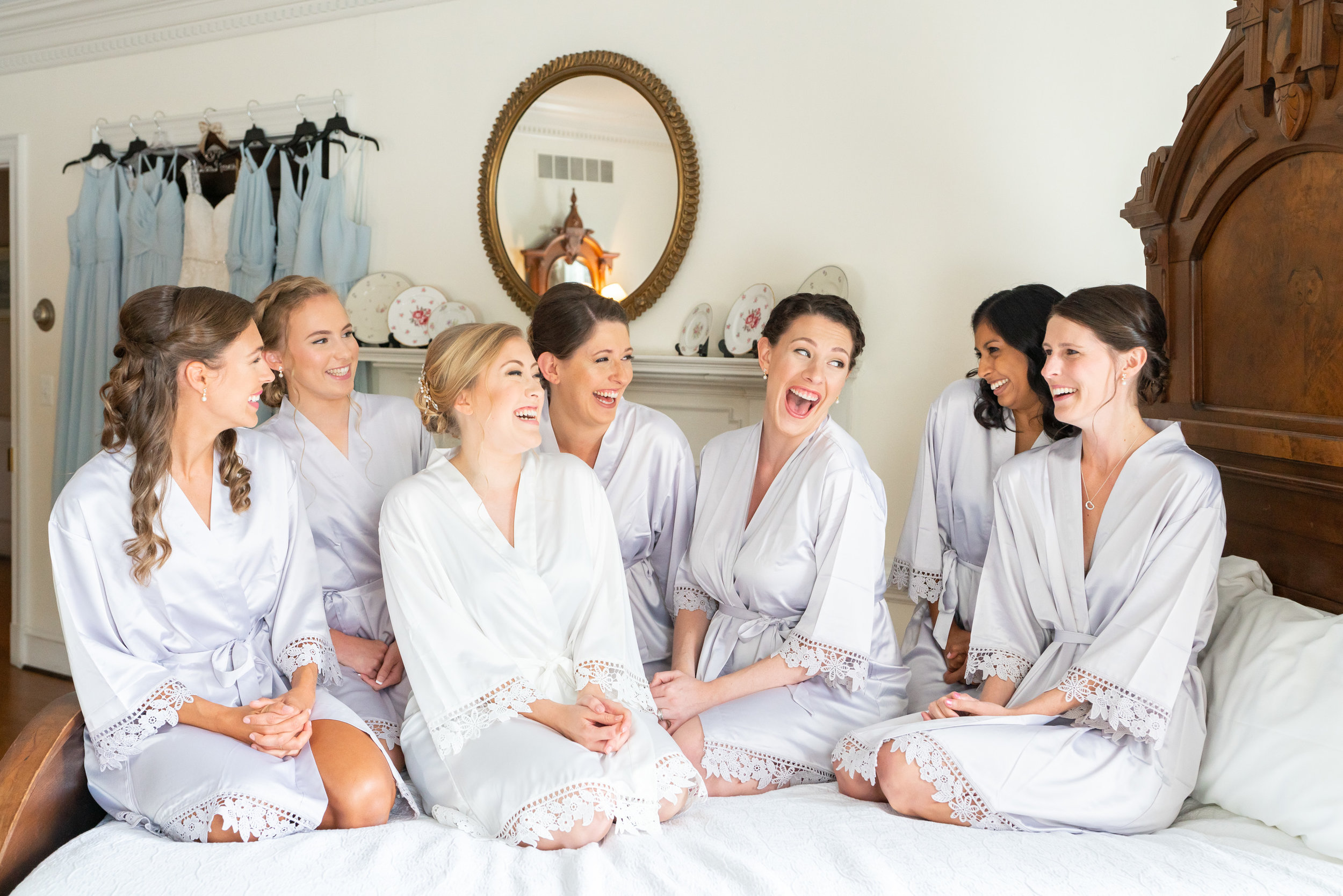 Bridesmaids and bride on bed laughing at Stone Manor Country Club