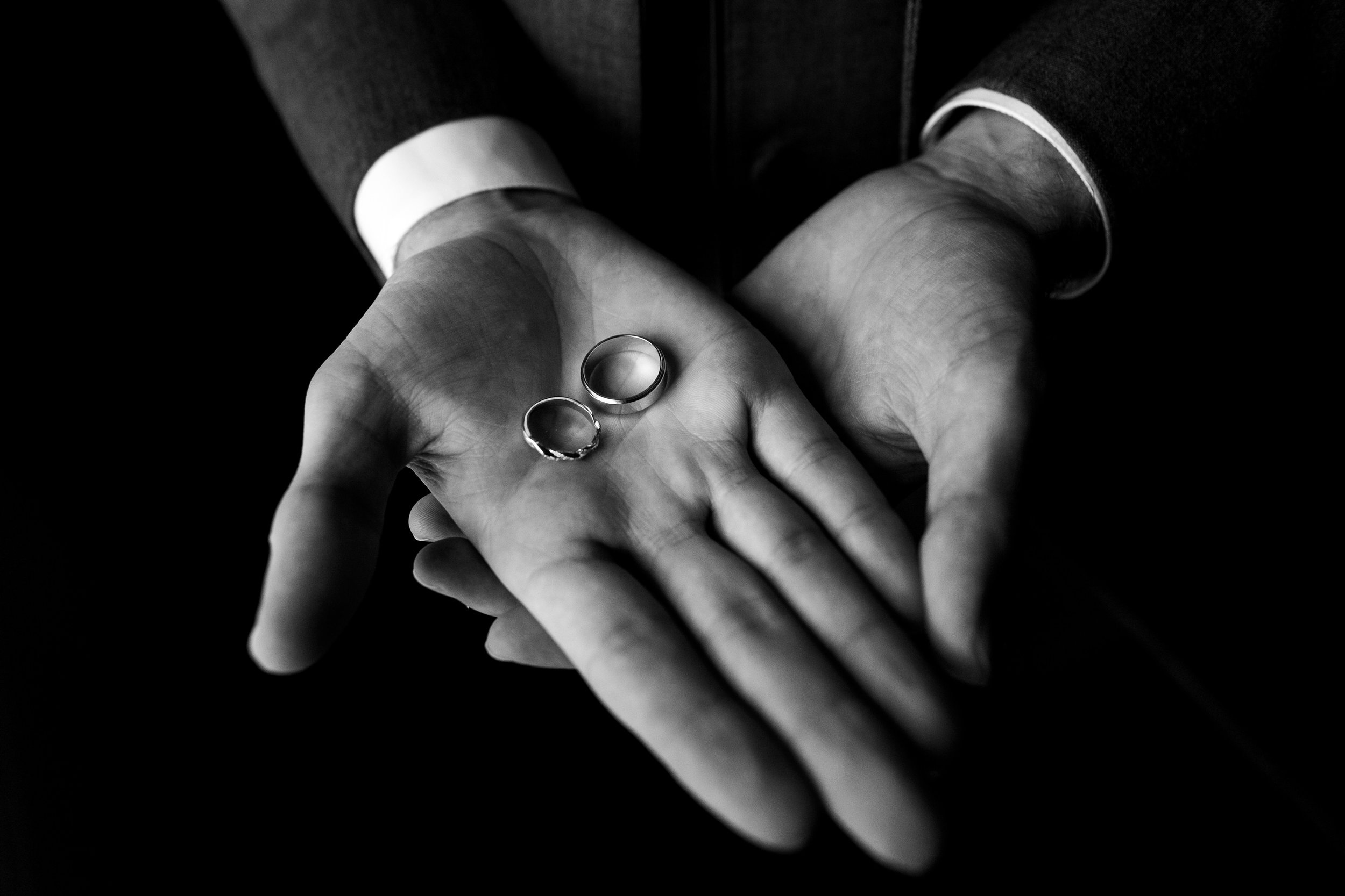 Wedding bands in grooms hand at Stone Manor Country Club