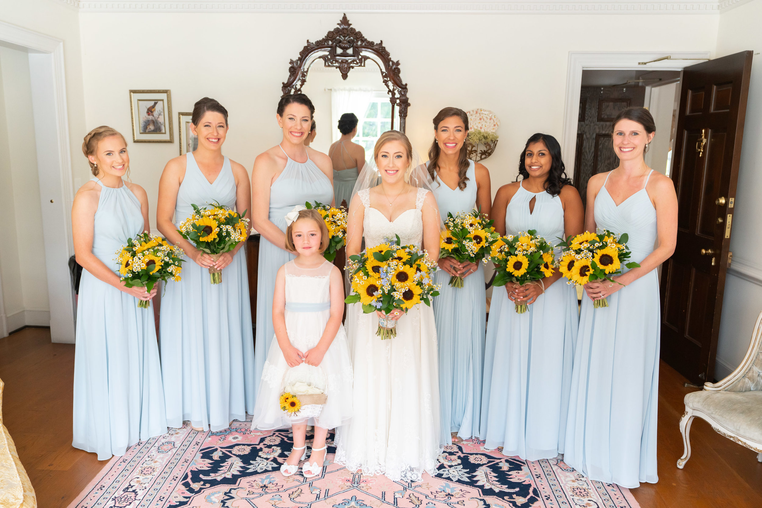 Sunflower bouquets and light blue Azazie dresses at Stone Manor Country Club