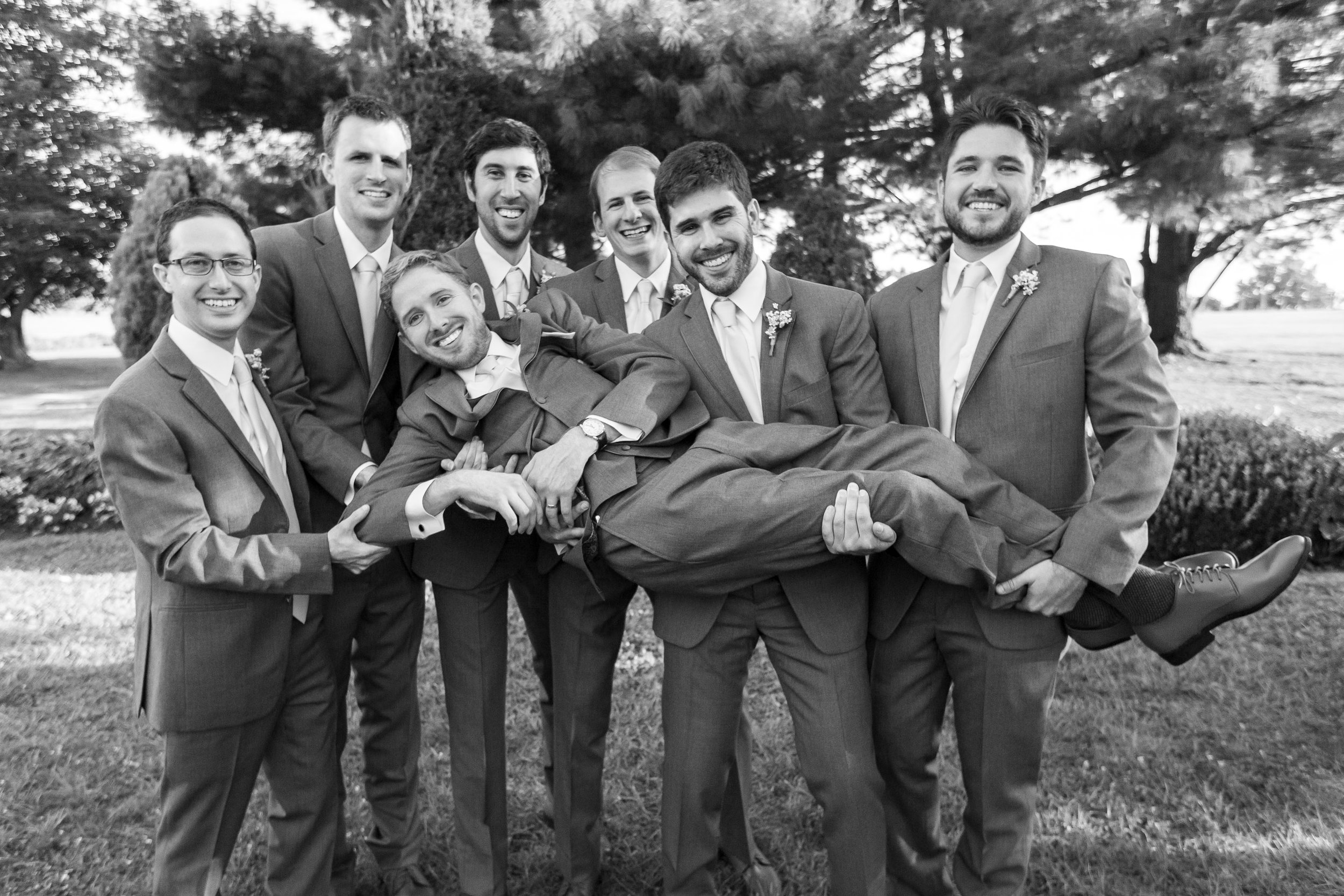 Groomsmen holding groom up at Stone Manor Country Club