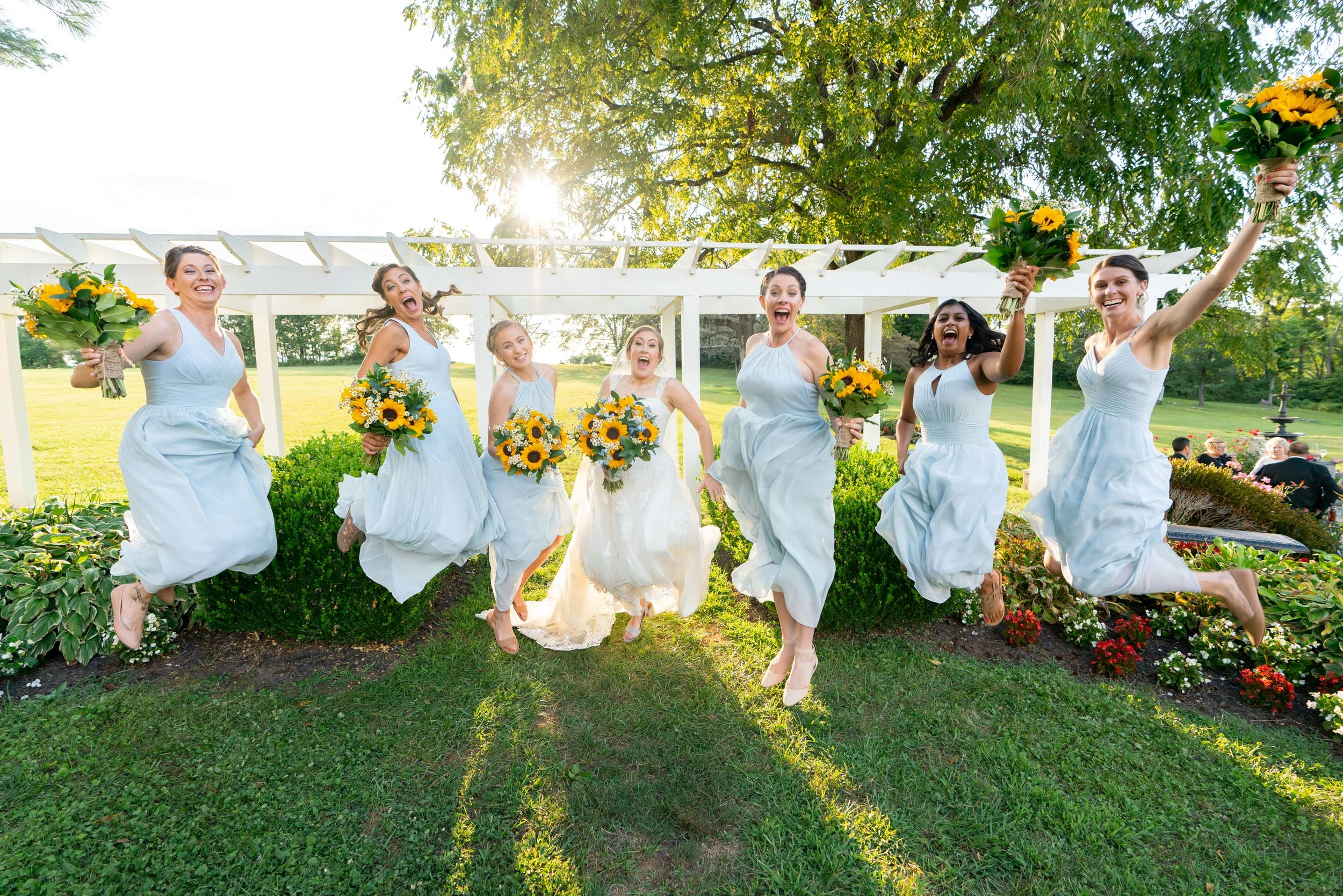 Bride and bridesmaids jumping in the air photo with blue azazie gowns