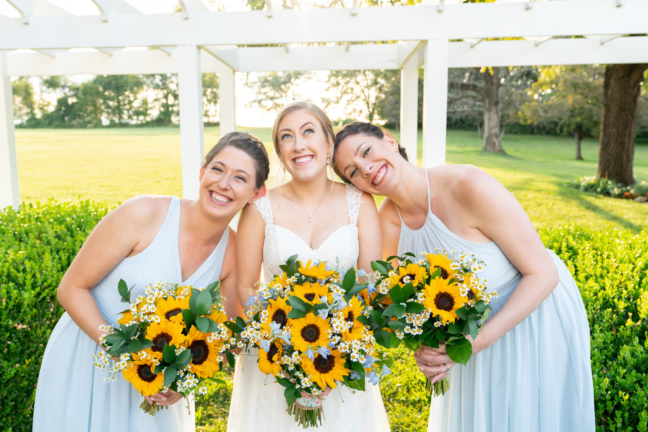 Bride and bridesmaids in blue azazie and sunflower bouquets at Frederick wedding venue
