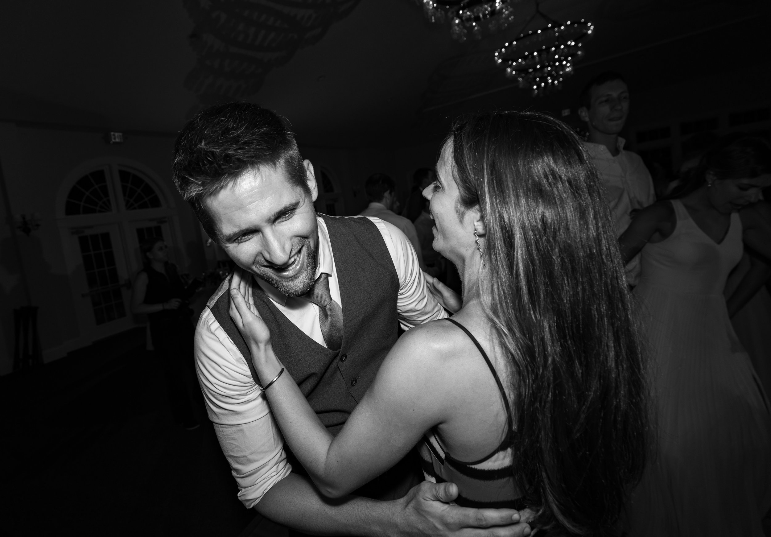 black and white photo of guests dancing during wedding reception