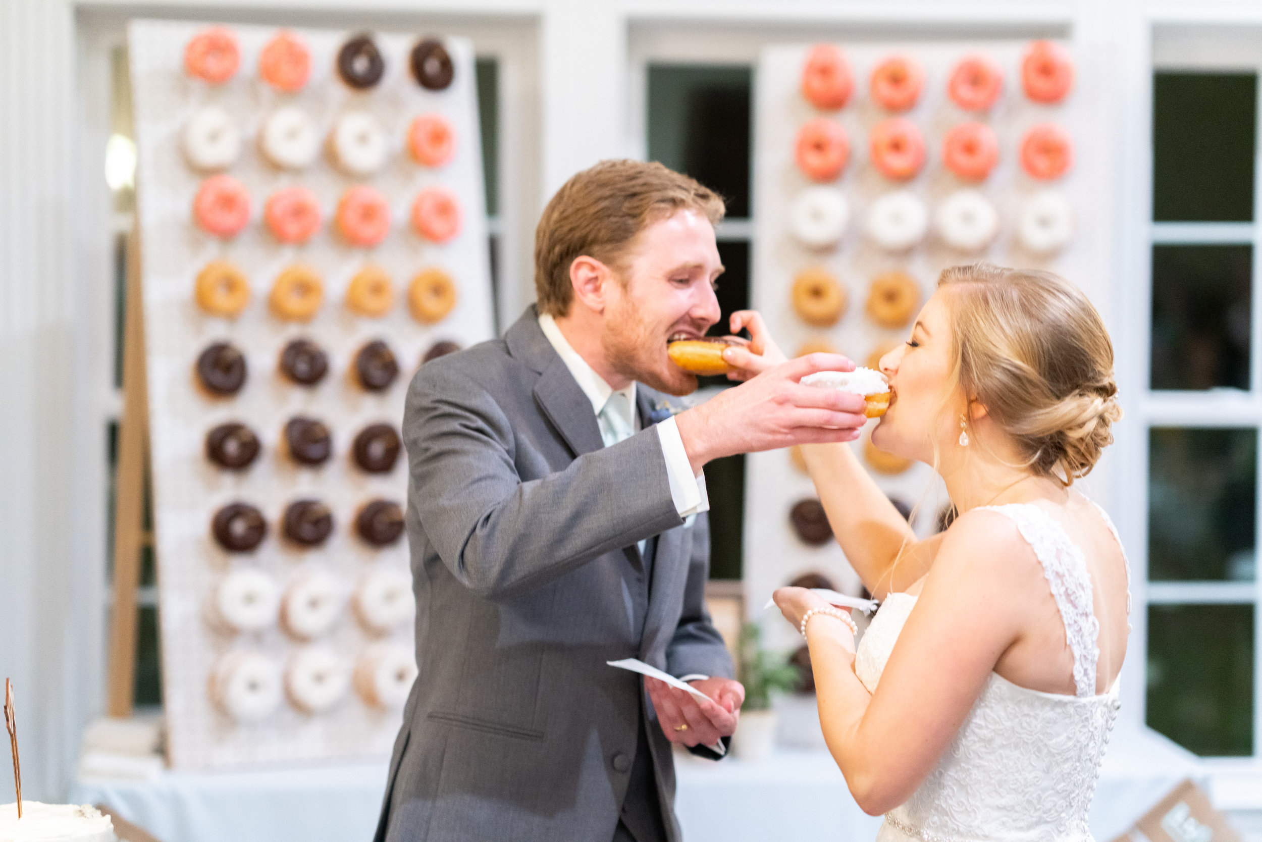 Bride and groom sharing donuts during cake cutting at stone manor country club