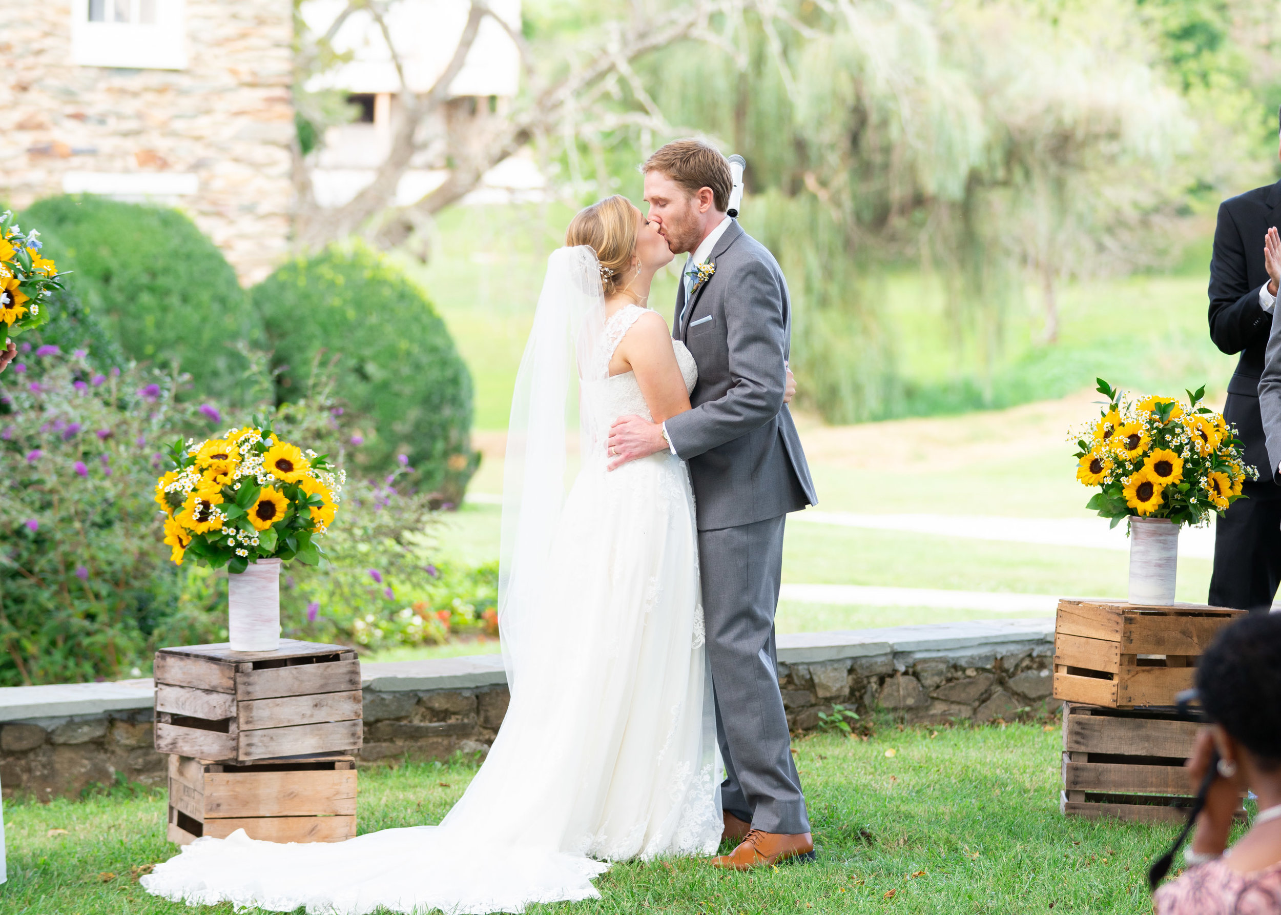 Bride and groom kissing during ceremony at Stone Manor Country Club