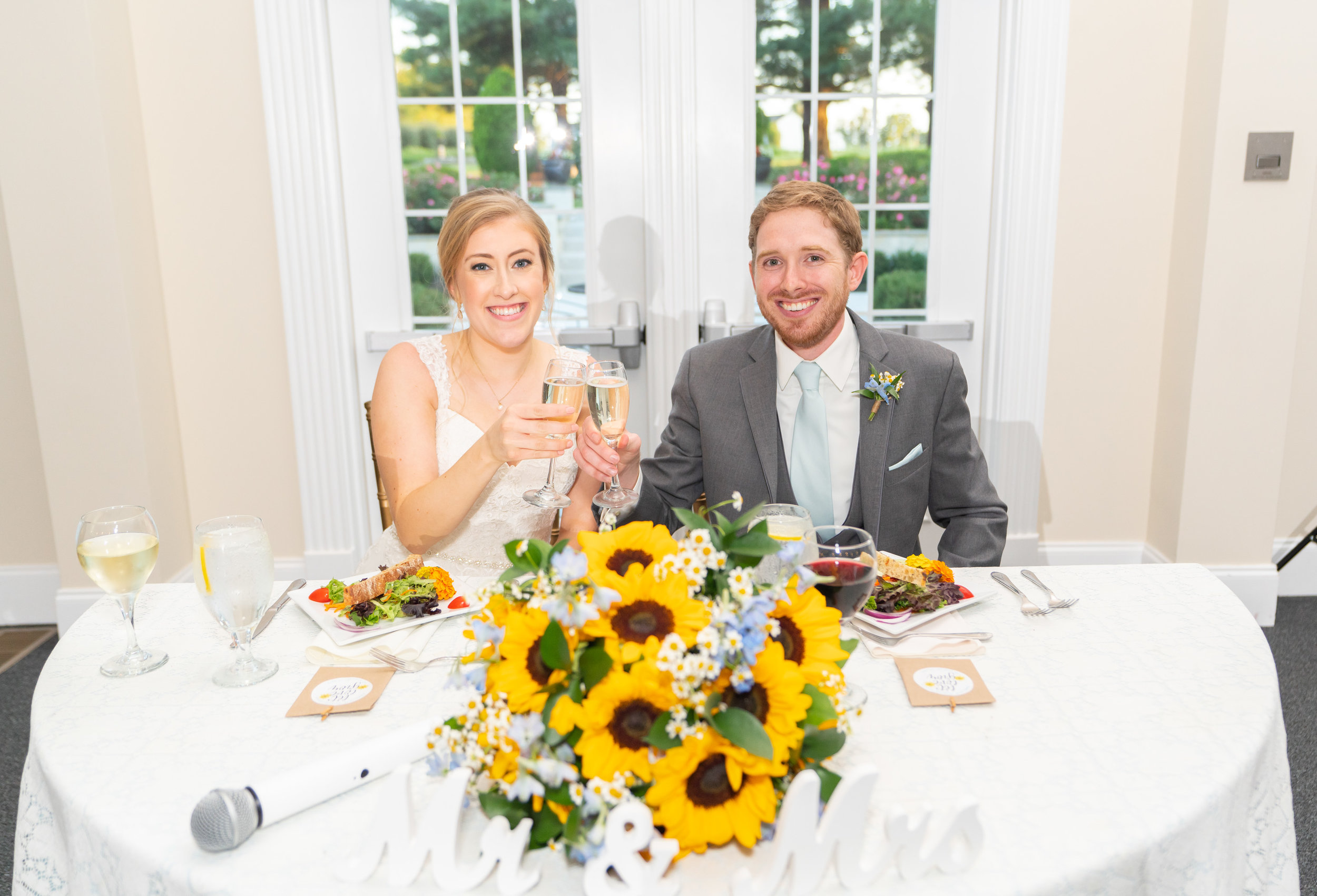 Bride and groom toast at sweetheart table with sunflower bouquet