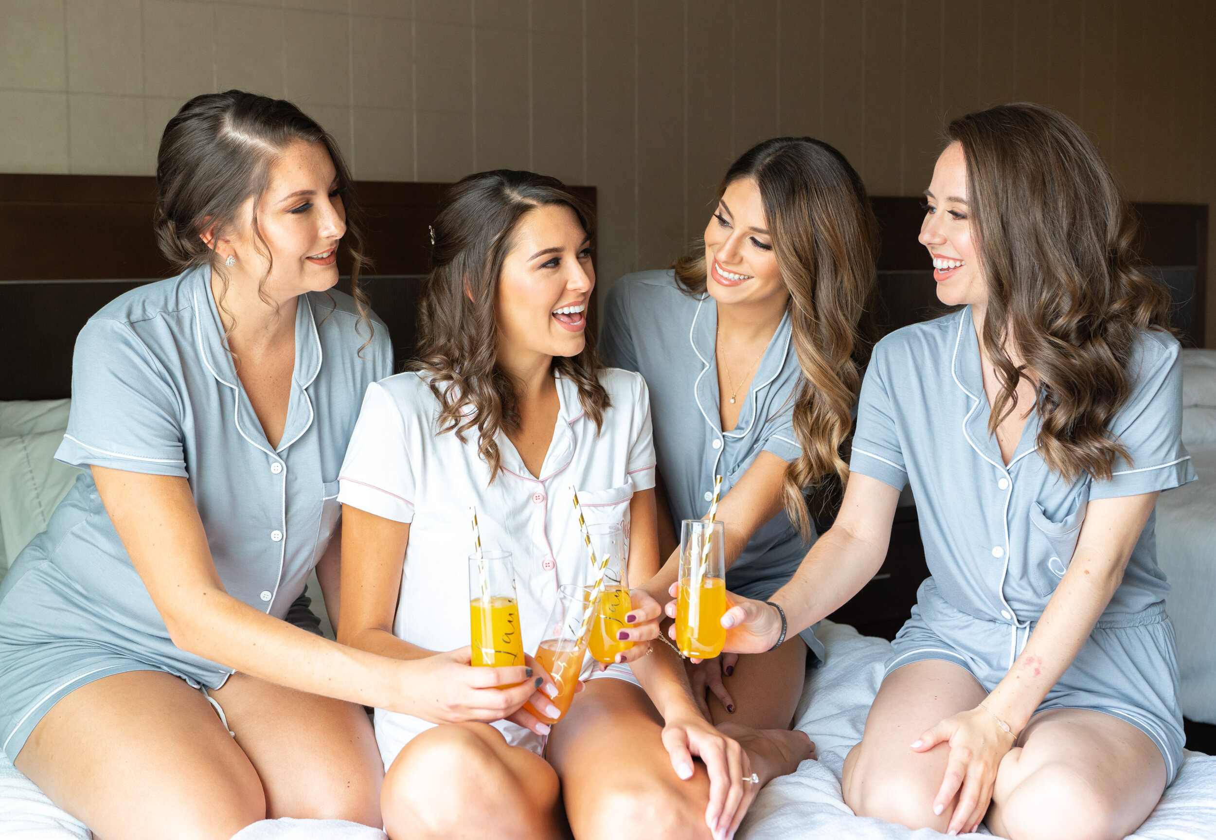Bride and bridesmaids in matching pajamas toasting mimosas on the bed at Embassy Suites Springfield