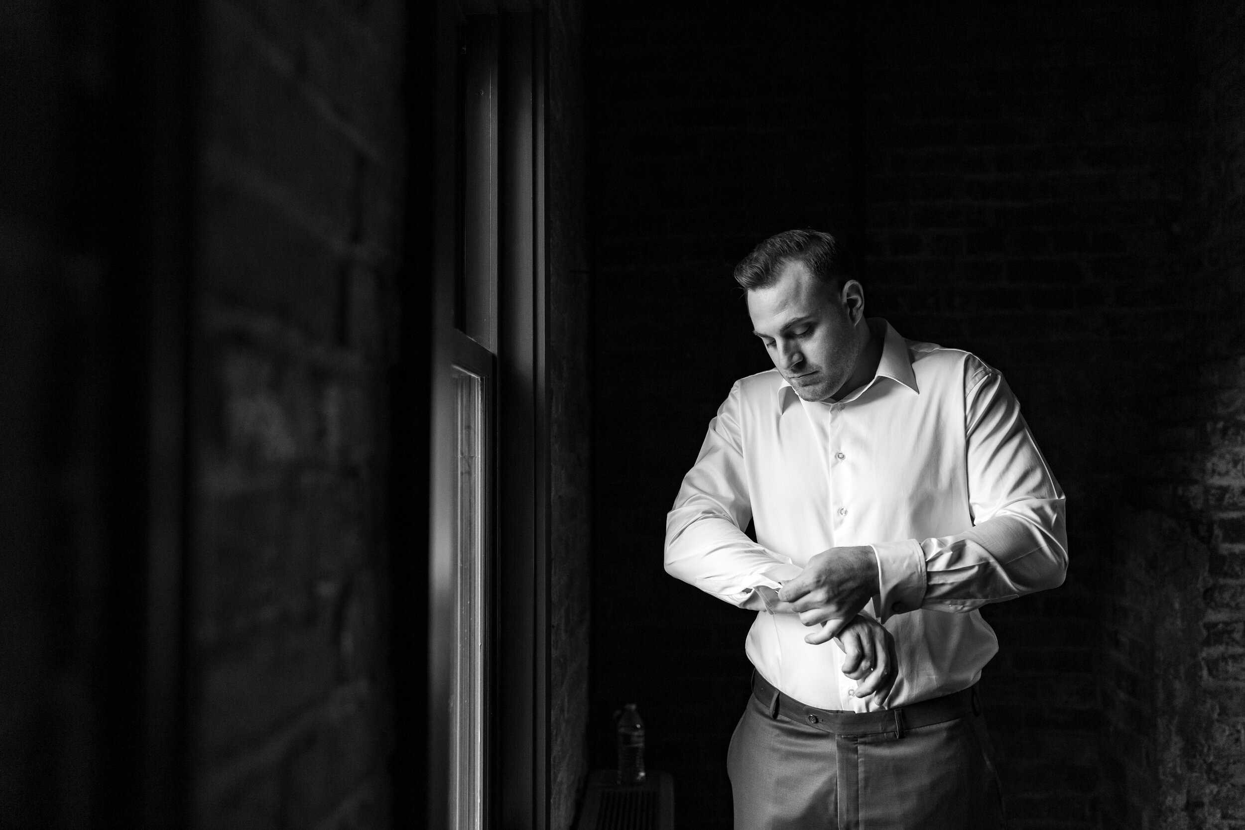 Groom doing cuff links in dramatic window light at Riverview at Occoquan