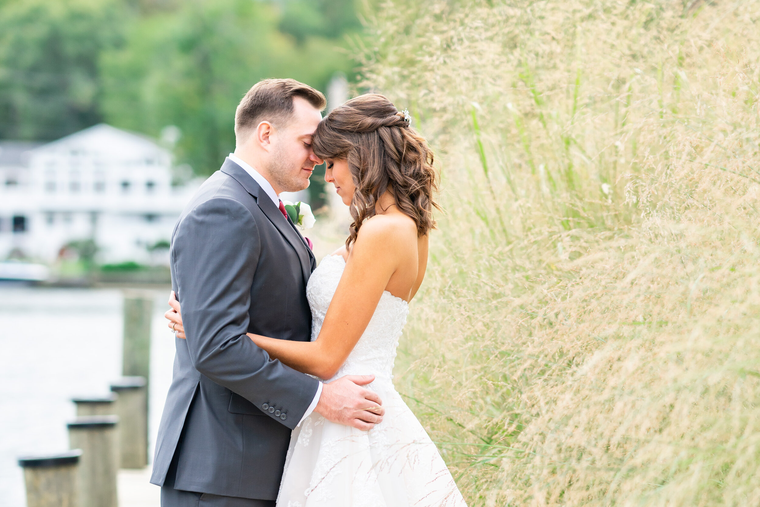 Bride and groom touching foreheads on the dock at Occoquan regional park