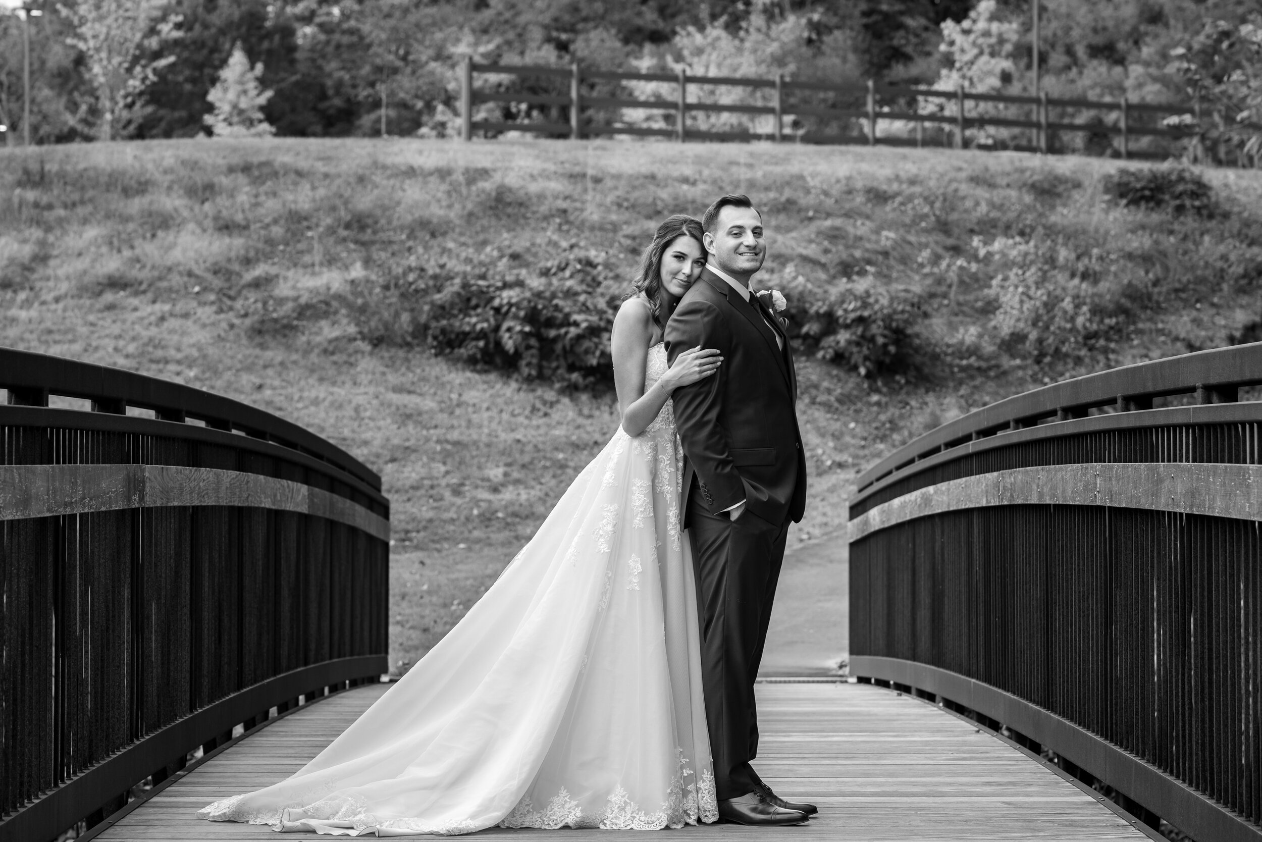 Bride snuggling groom on the bridge behind Riverview at Occoquan