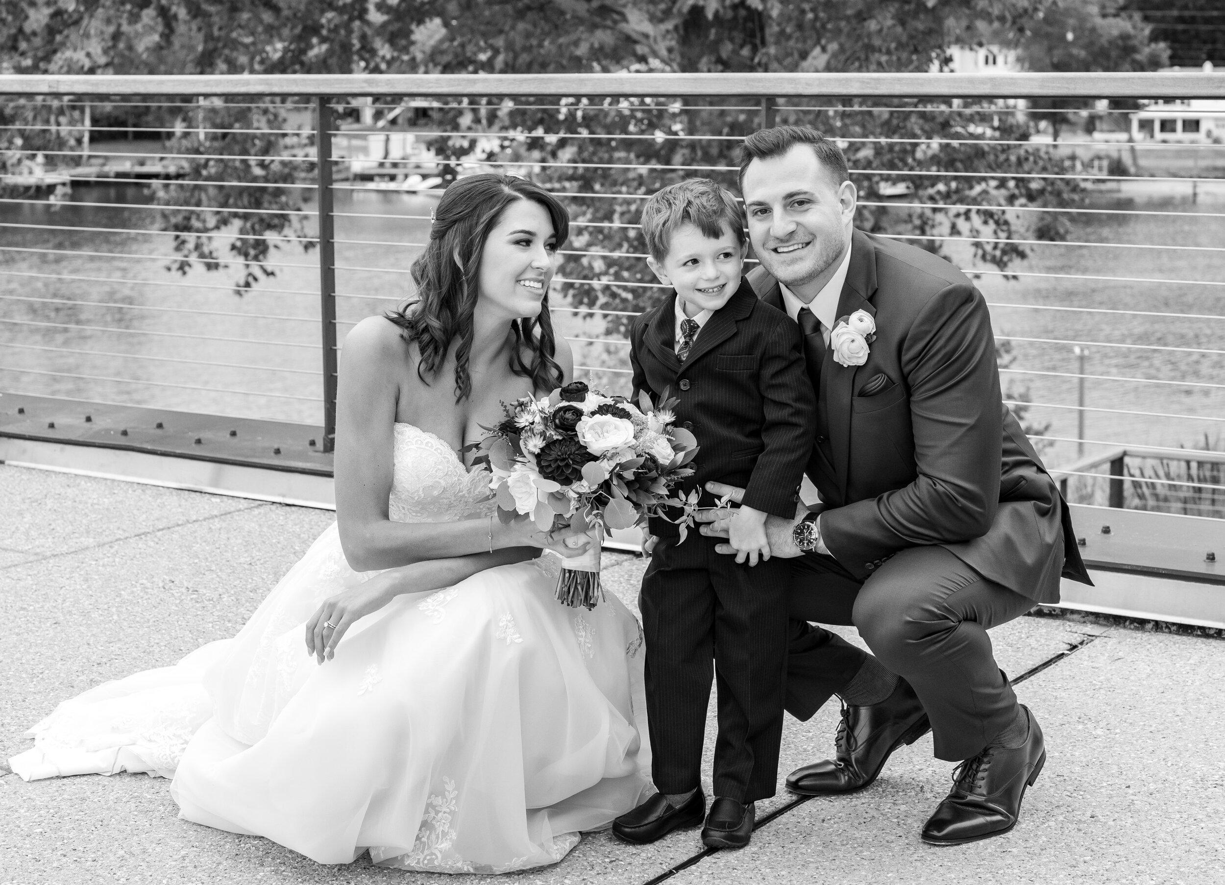 Bride and groom hugging nephew ring bearer