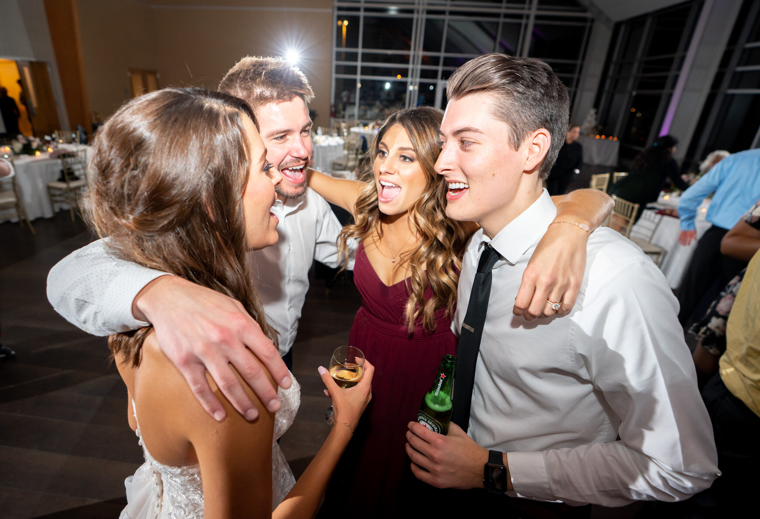 Bride and guests hugging on the dance floor with DJ Luccio