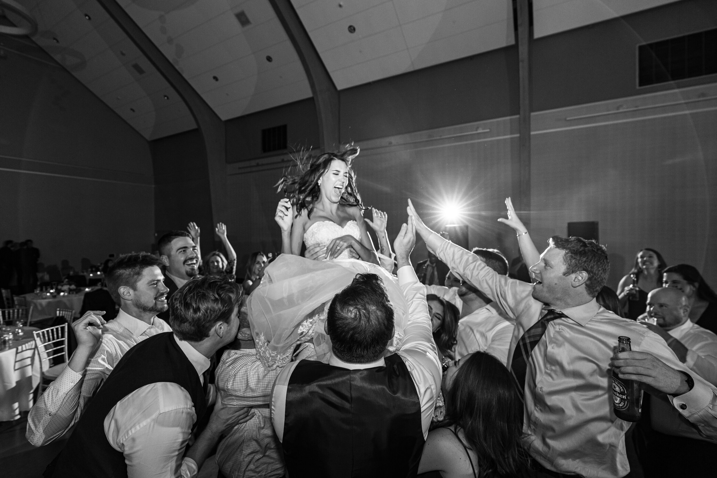 Bride being lifted into the air during crazy wedding reception