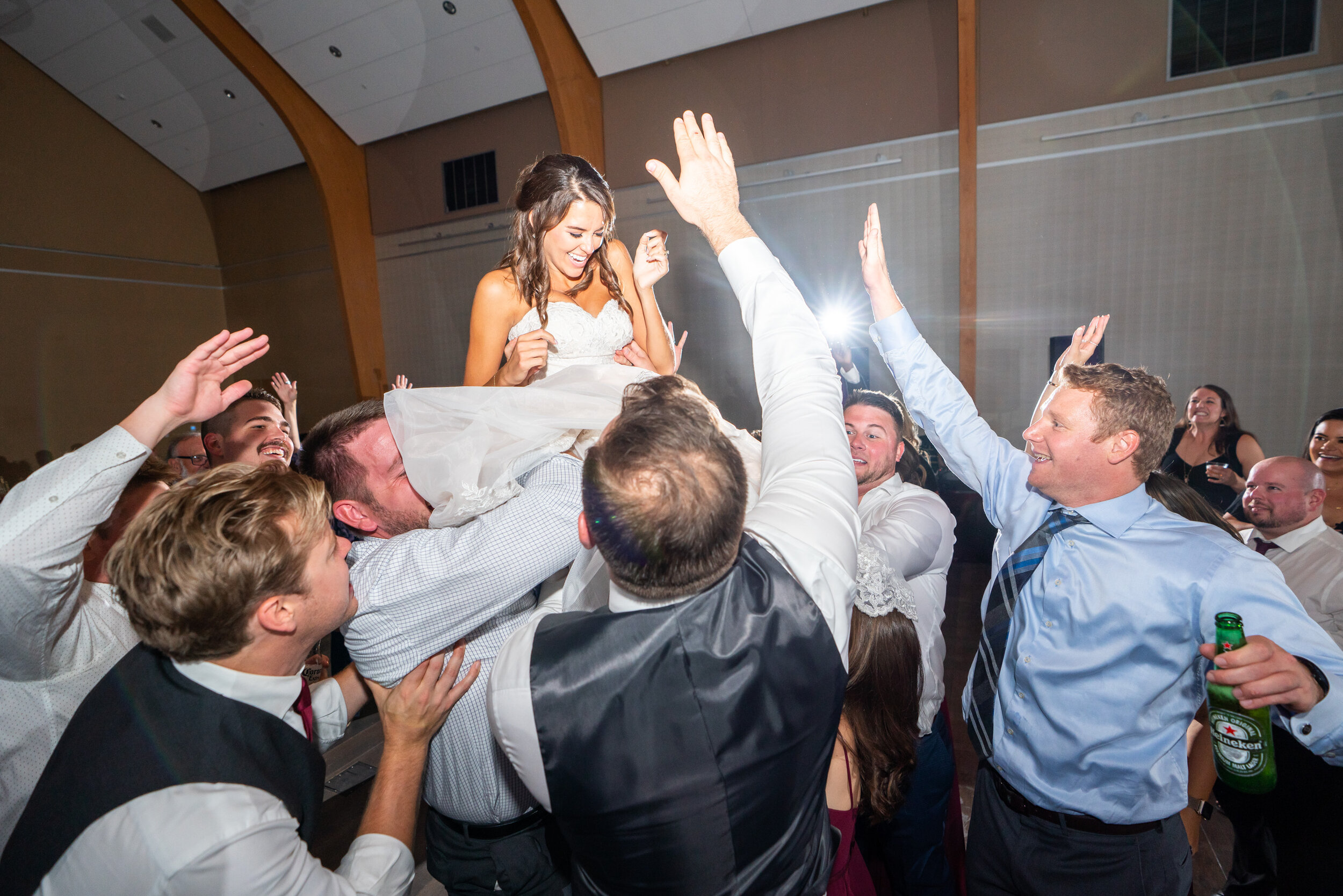 Bride being tossed in the air by groomsmen at Riverview at Occoquan
