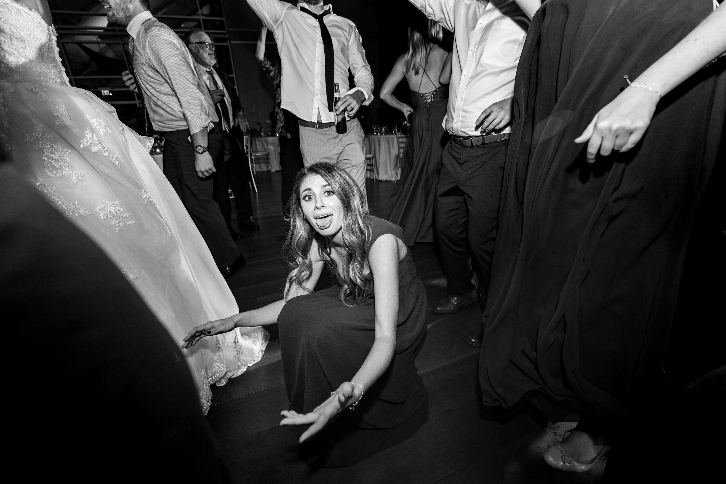 Bridesmaid putting sneakers on the bride on the dance floor