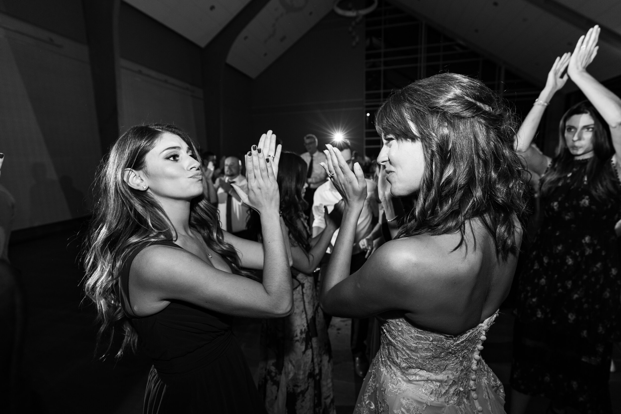 Bride and bridesmaid clapping and dancing during wedding reception