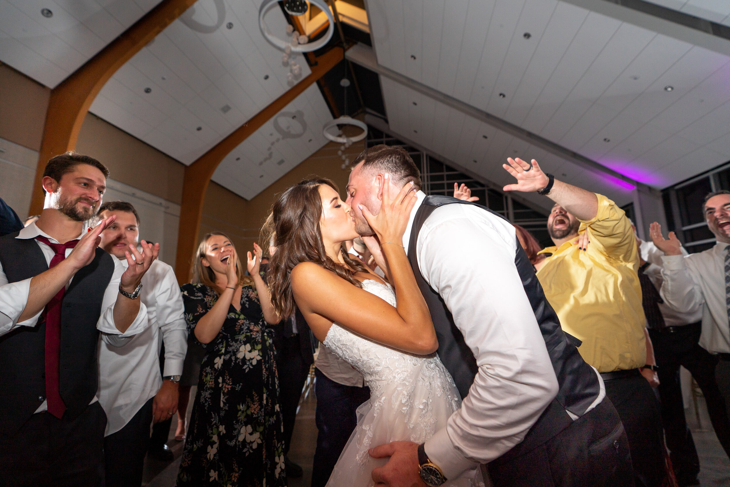 Bride and groom kissing in the circle of their friends during the last song