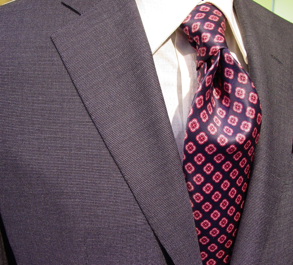 Grey single breasted interview suit with small pattern tie.