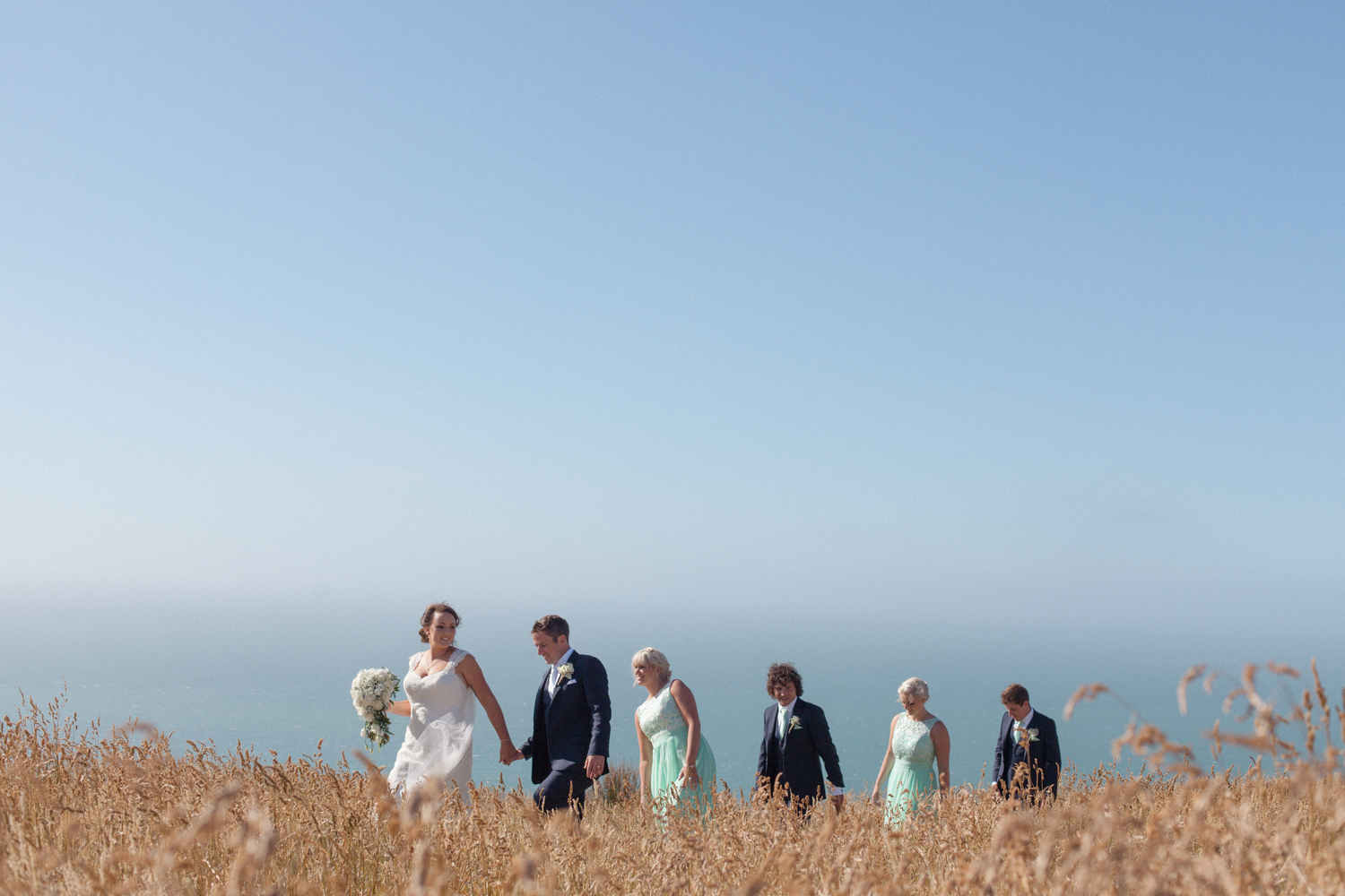 Bridal party walking through long grass at Boomrock wedding venue