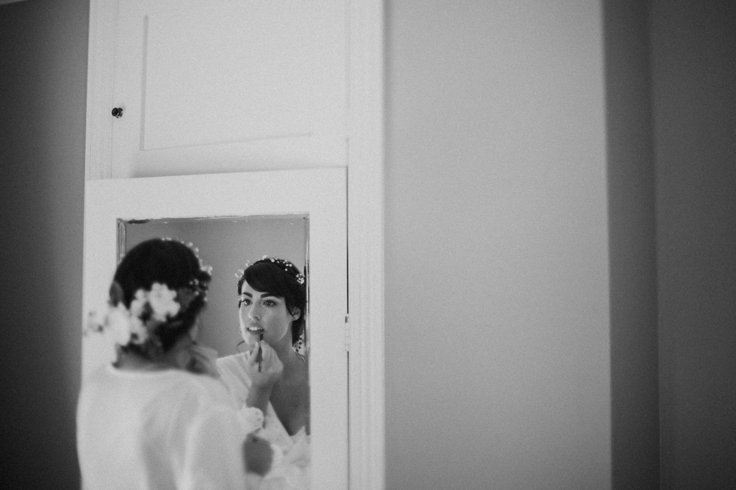 Bride putting on her make up in the mirror