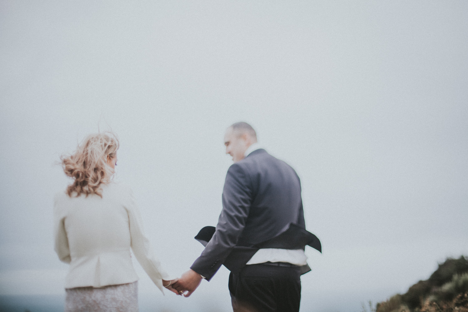 Bride and Groom holding hands as they look out at the oceans view