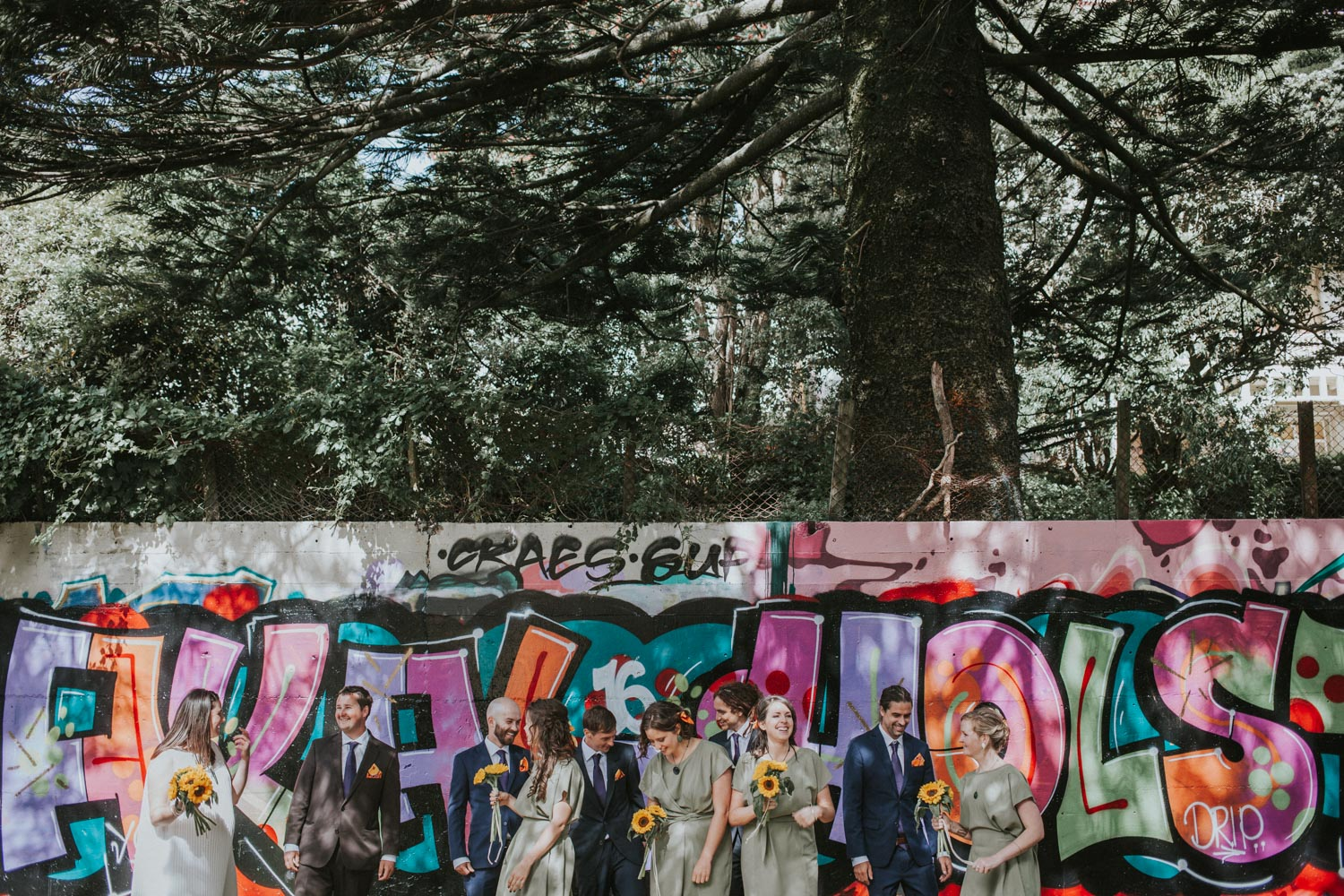 Bridal party standing in front of Graffiti wall for bridal photos