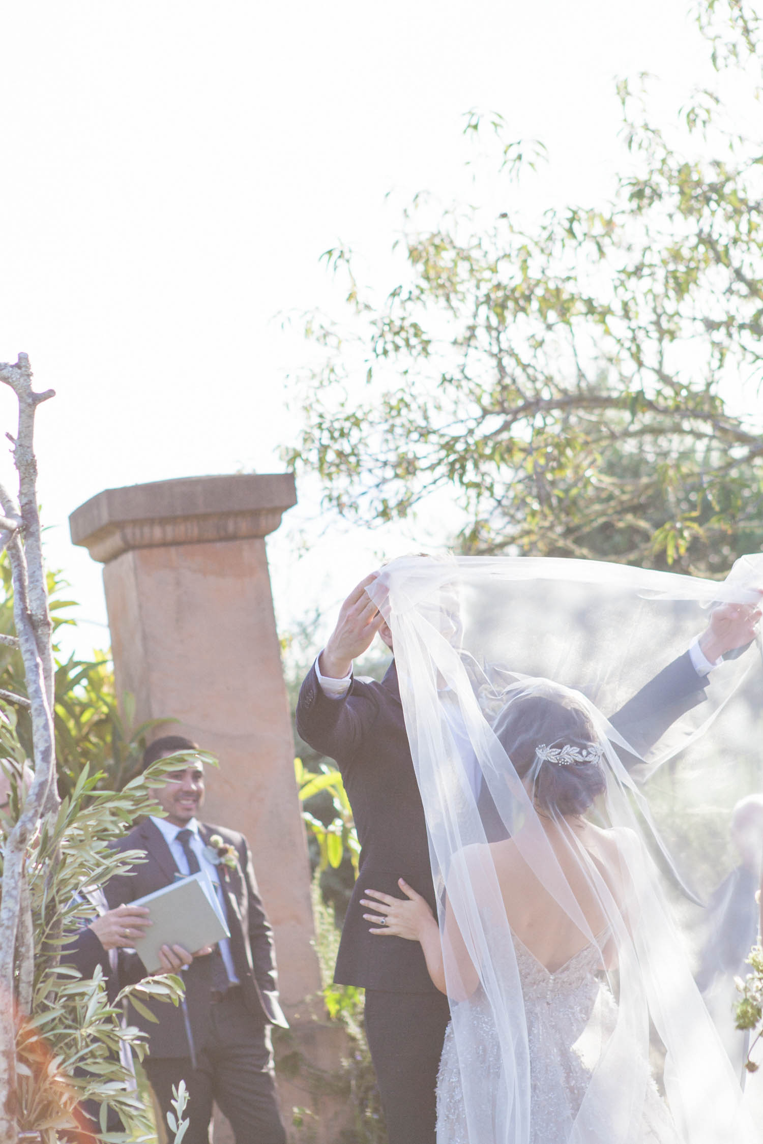 Groom takes off his Brides wedding veil to kiss her