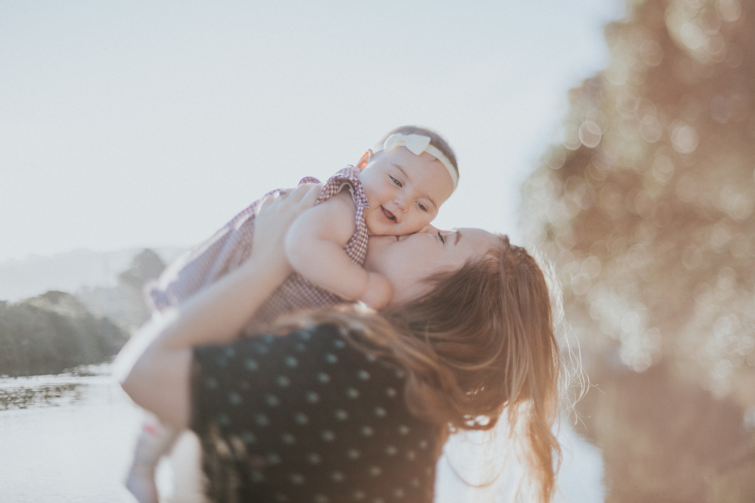Mother kissing baby girl in the sun