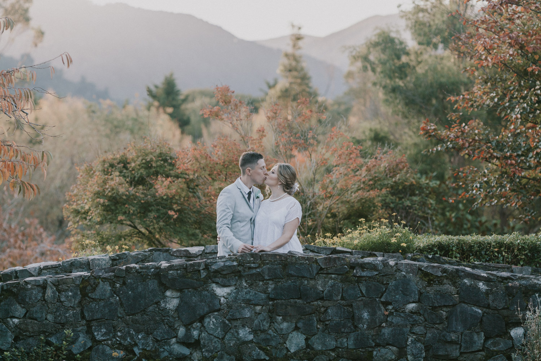 Bride and Groom kissing on stone bridge at Aston Norwood Gardens