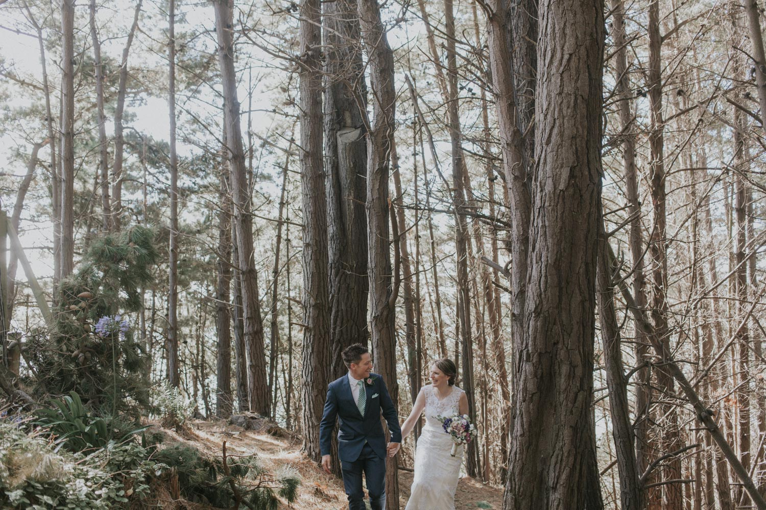 Newly weds walking through forest holding hands