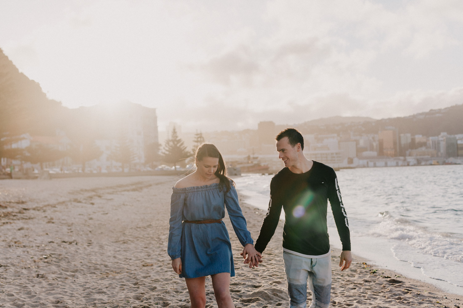 Engaged couple walking along the beach down Oriental Parade in Wellington
