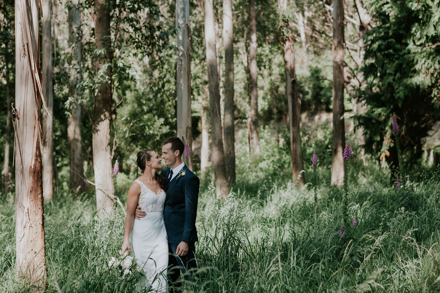 Bride and Groom standing in long grass