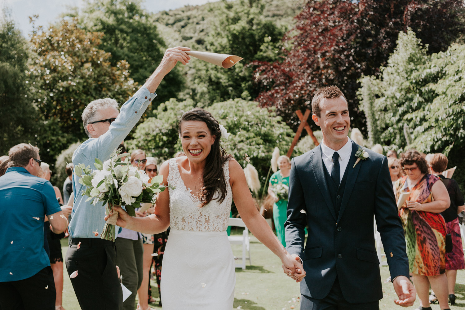 Guests throwing flower petals over Bride and Groom