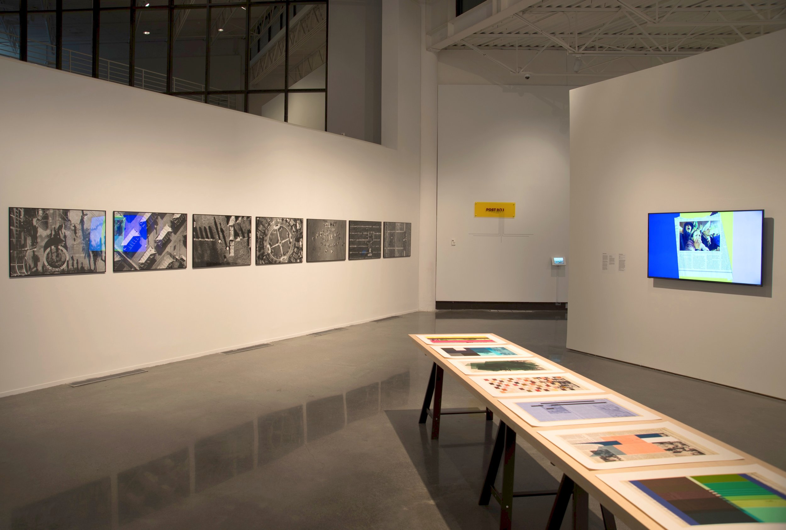 Dispatches exhibition, view of Tomas Van Houtryve's photo series,  Blue Sky Days , 2015, (Left) and a commissioned video work by Doug Ashford,  Bunker, (clippings 1982 to 2016, Group 1) , 2016, HD Video animation with sound, 5:40, (Right). Photo courtesy Southeastern Center for Contemporary Art.
